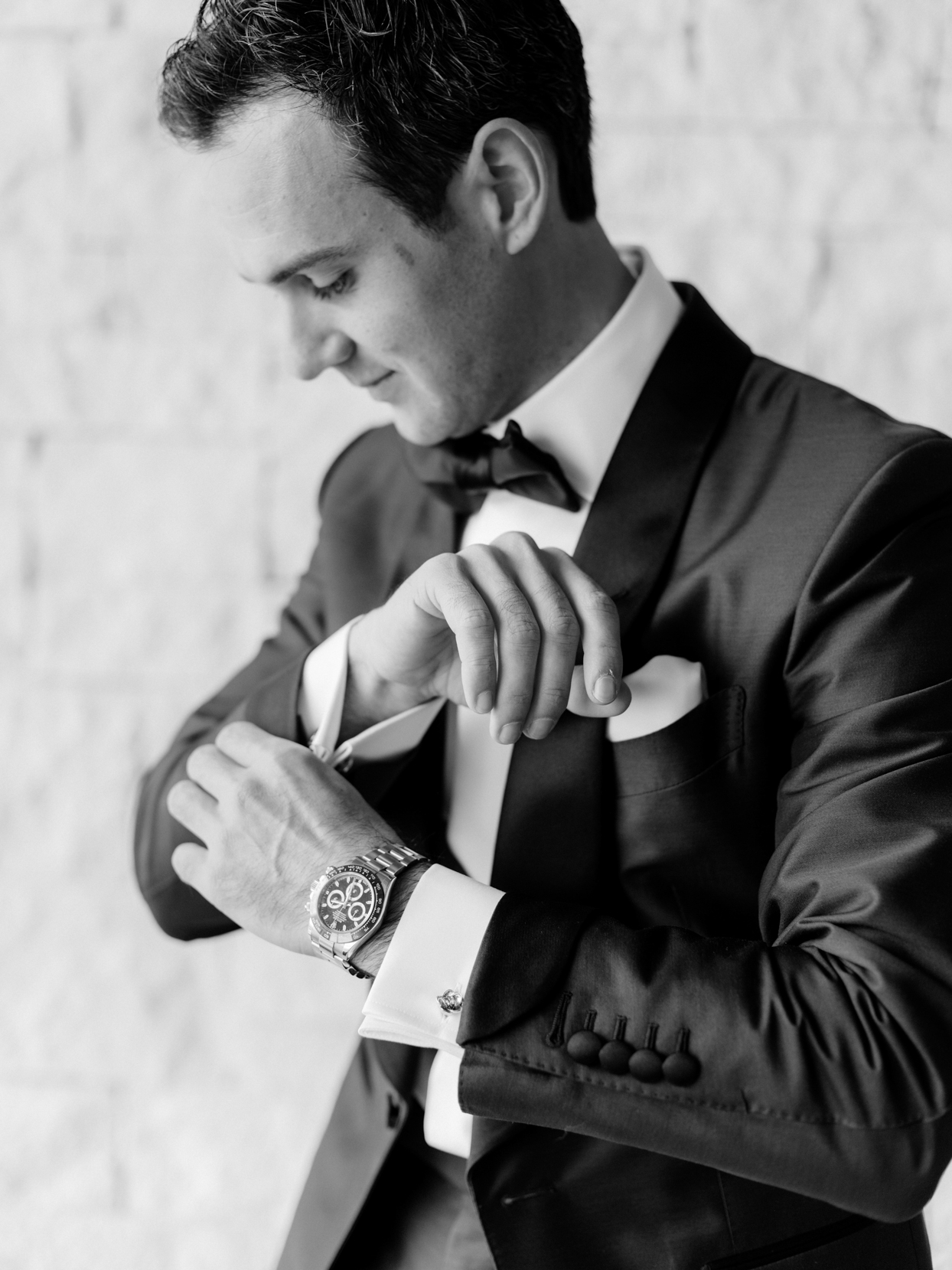 groom getting ready wearing watch and suit with bowtie