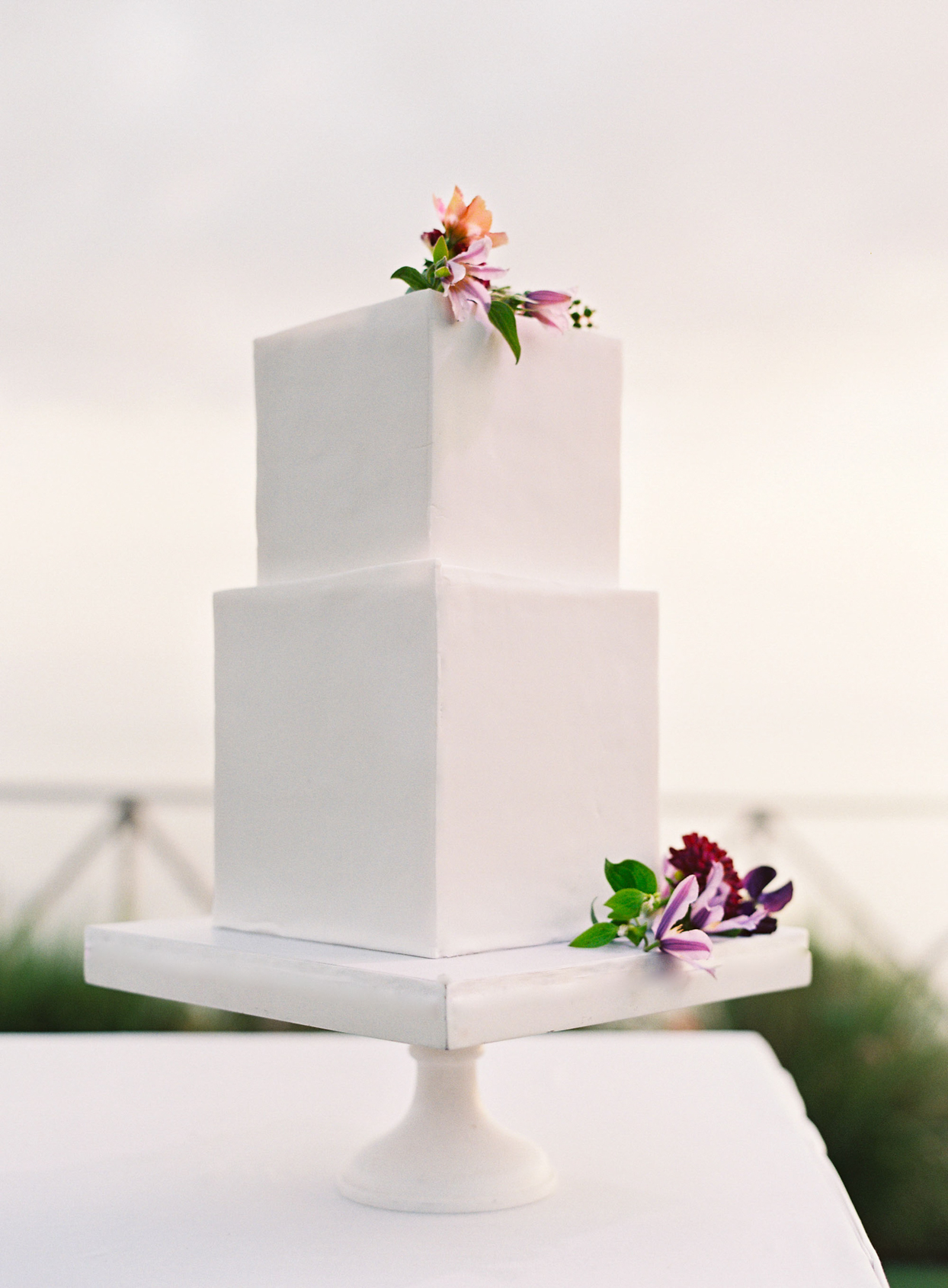 two tiered white frosted square wedding cake