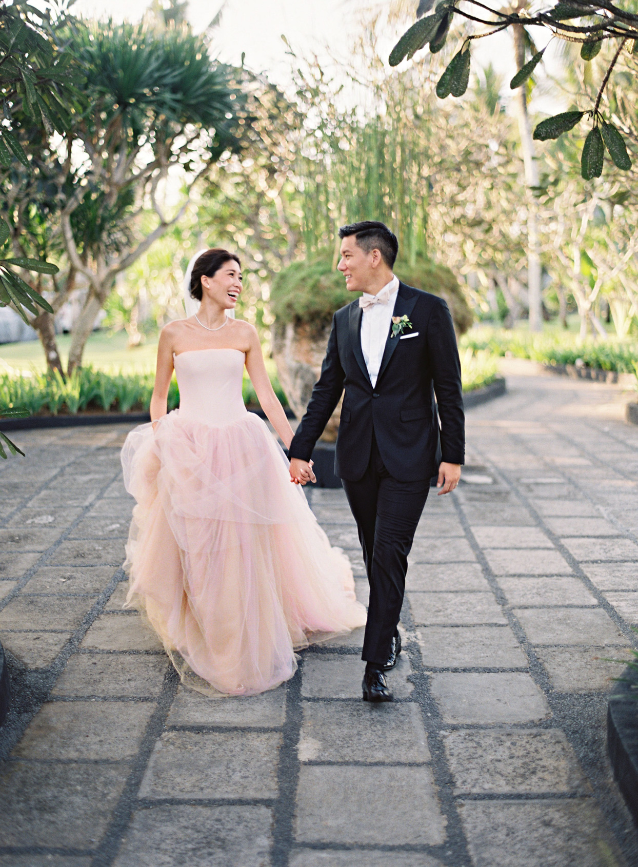 bride and groom holding hands smiling walking in stone paved garden area