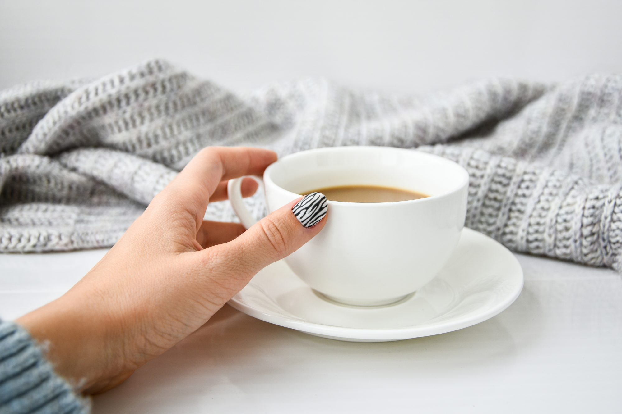 hand with manicure grabbing coffee cup