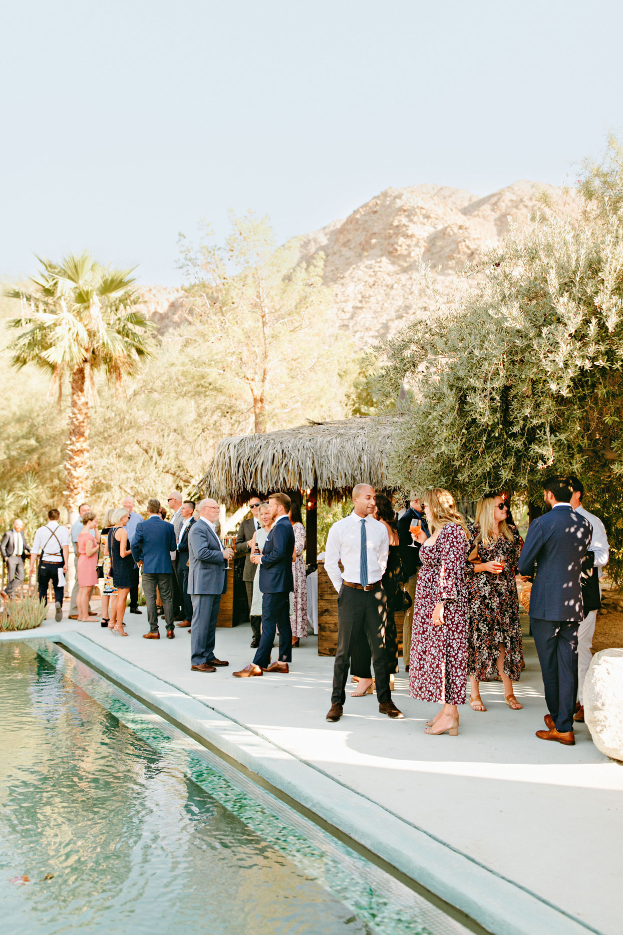 wedding guests enjoying cocktail hour by outdoor pool