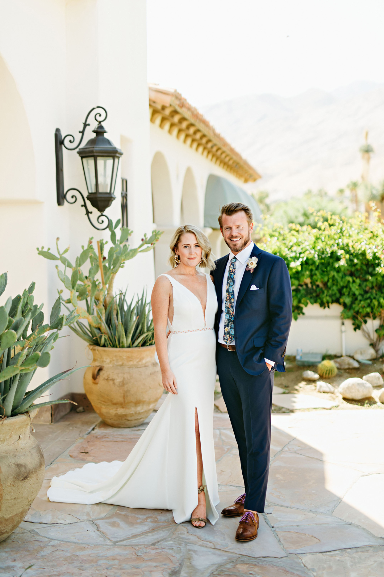 bride and groom posing in front of palm springs venue