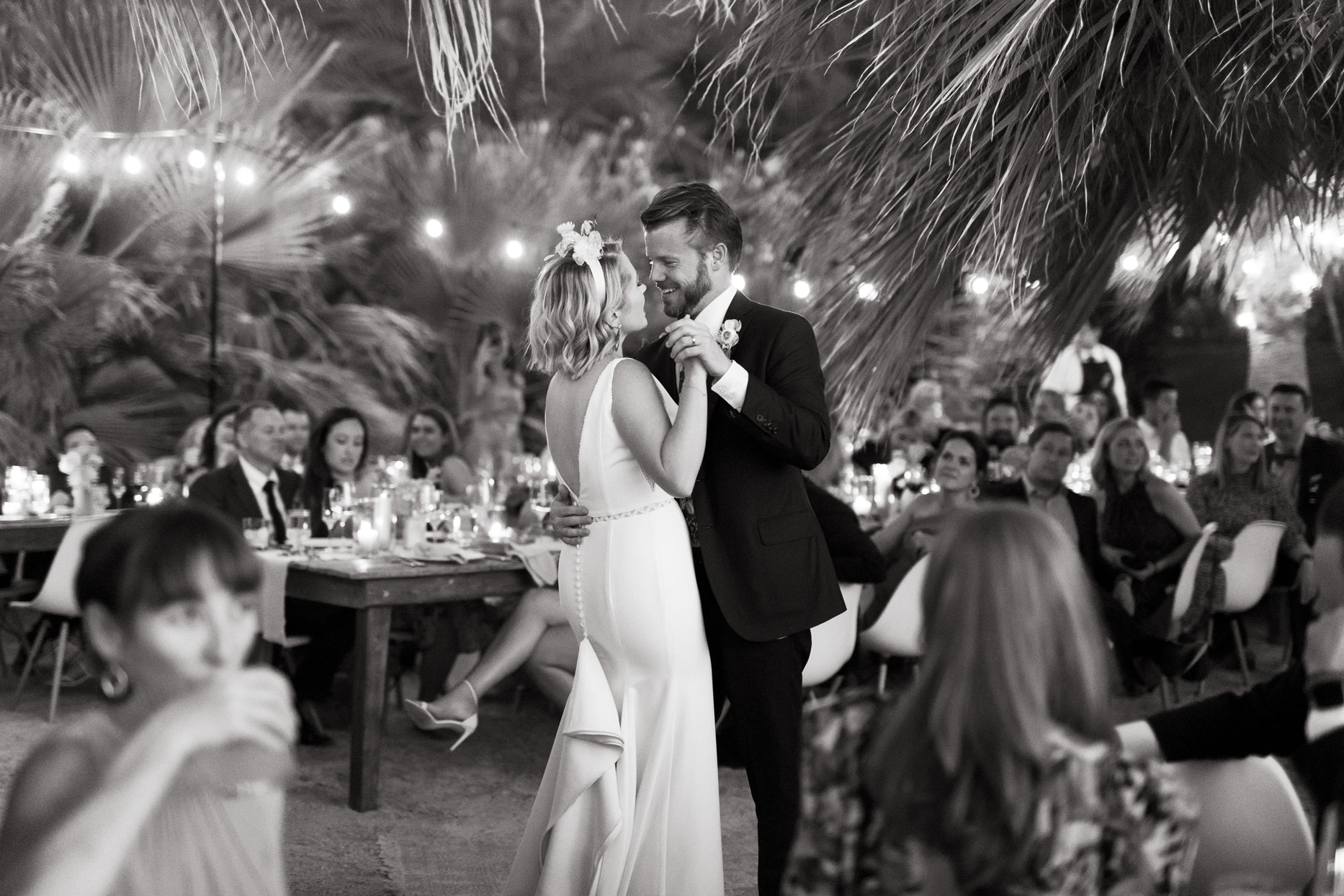 bride and groom sharing first dance beneath palm trees