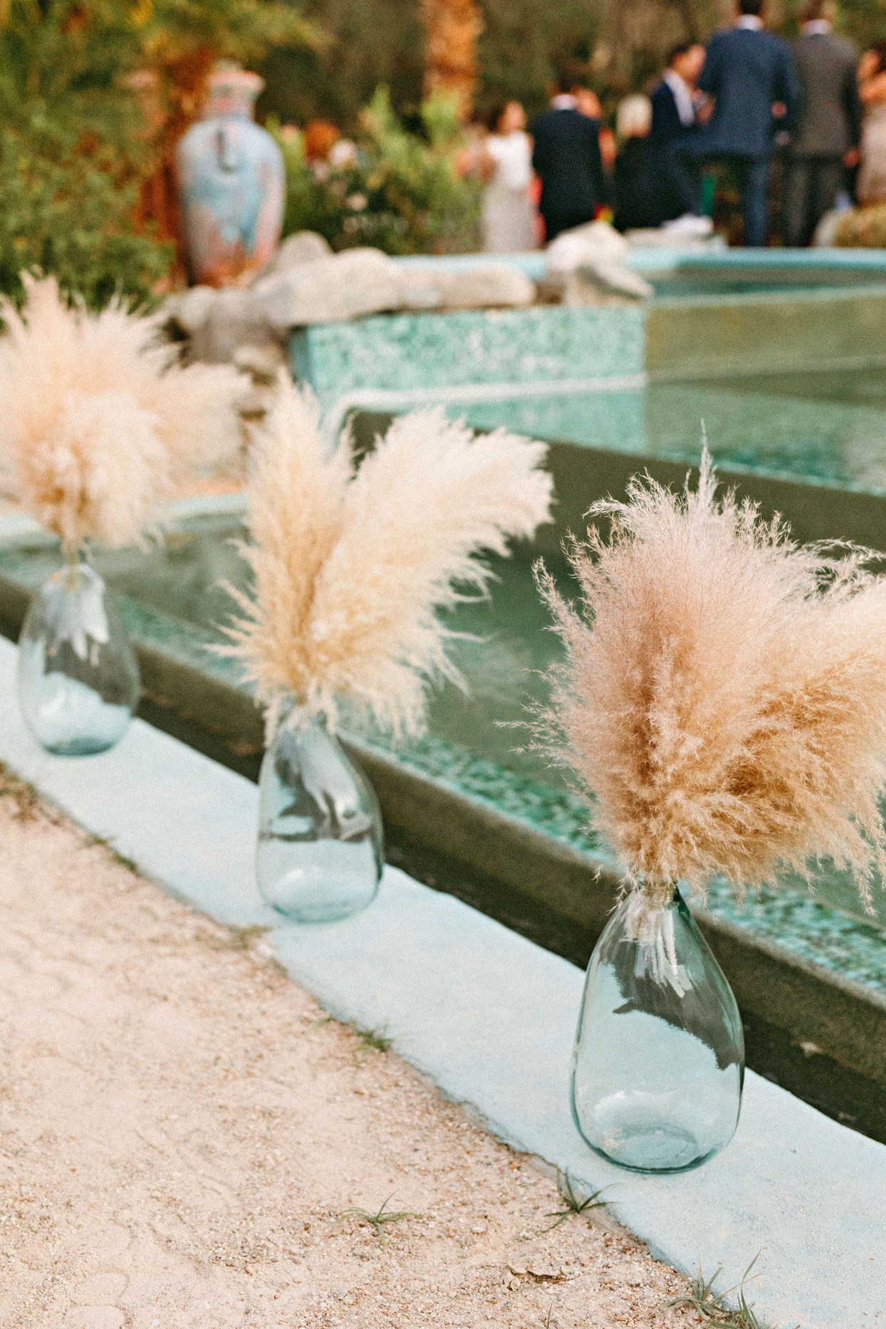 pampas grass and recycled glass vases lining aisle