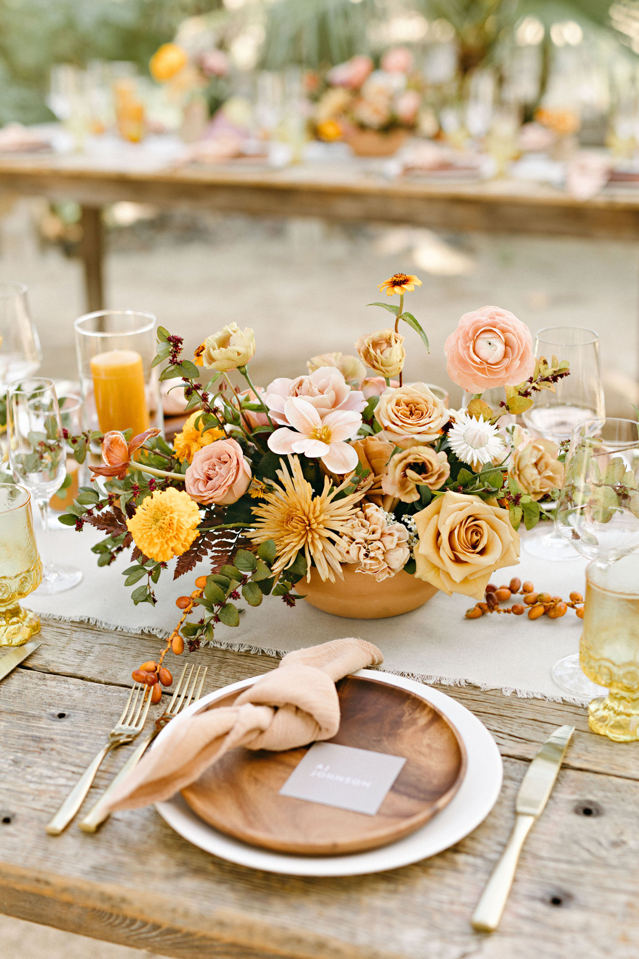 rustic wedding tablescape with gold flatware and wooden plates