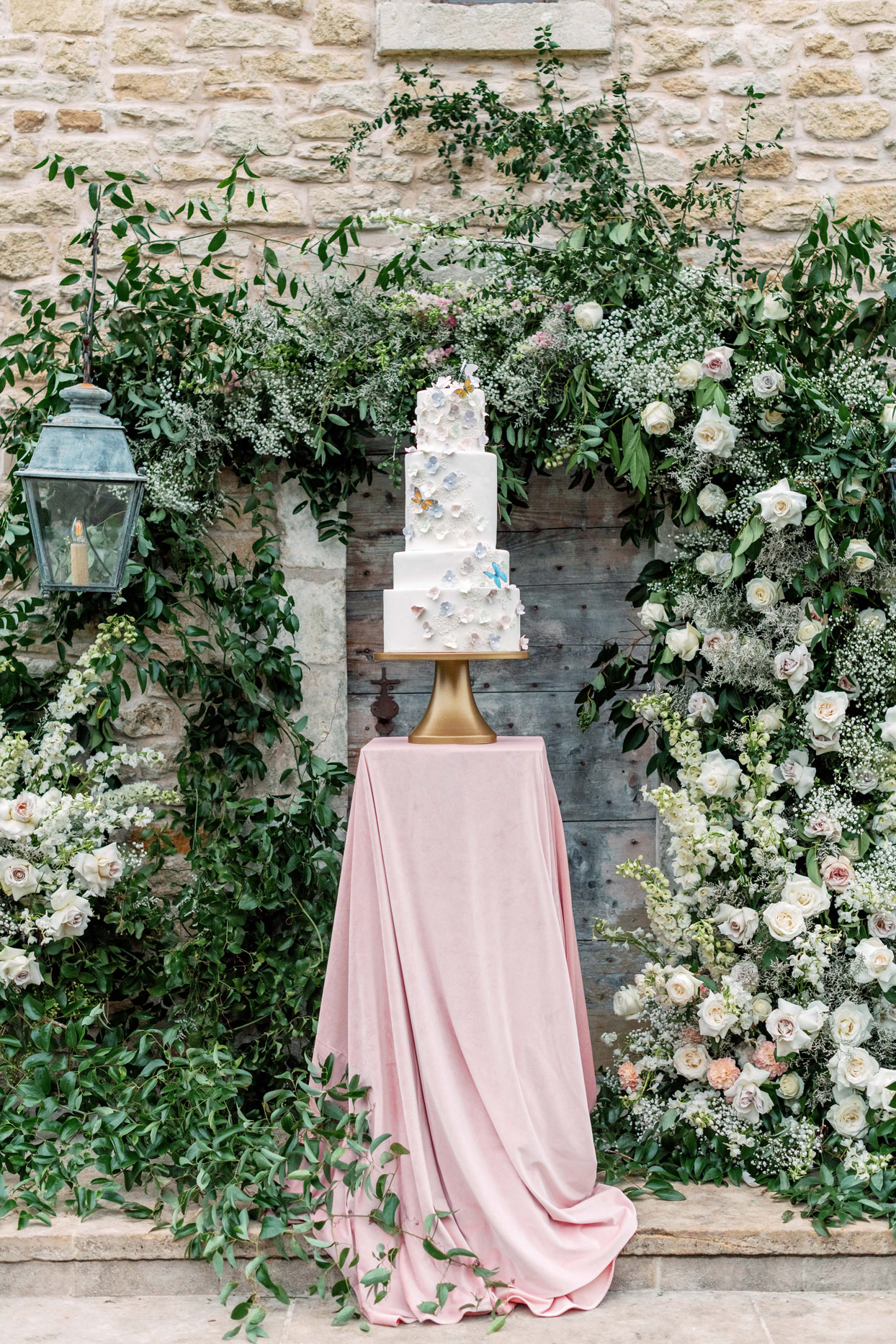 four-tier wedding cake on golden pedestal with blush tablecloth
