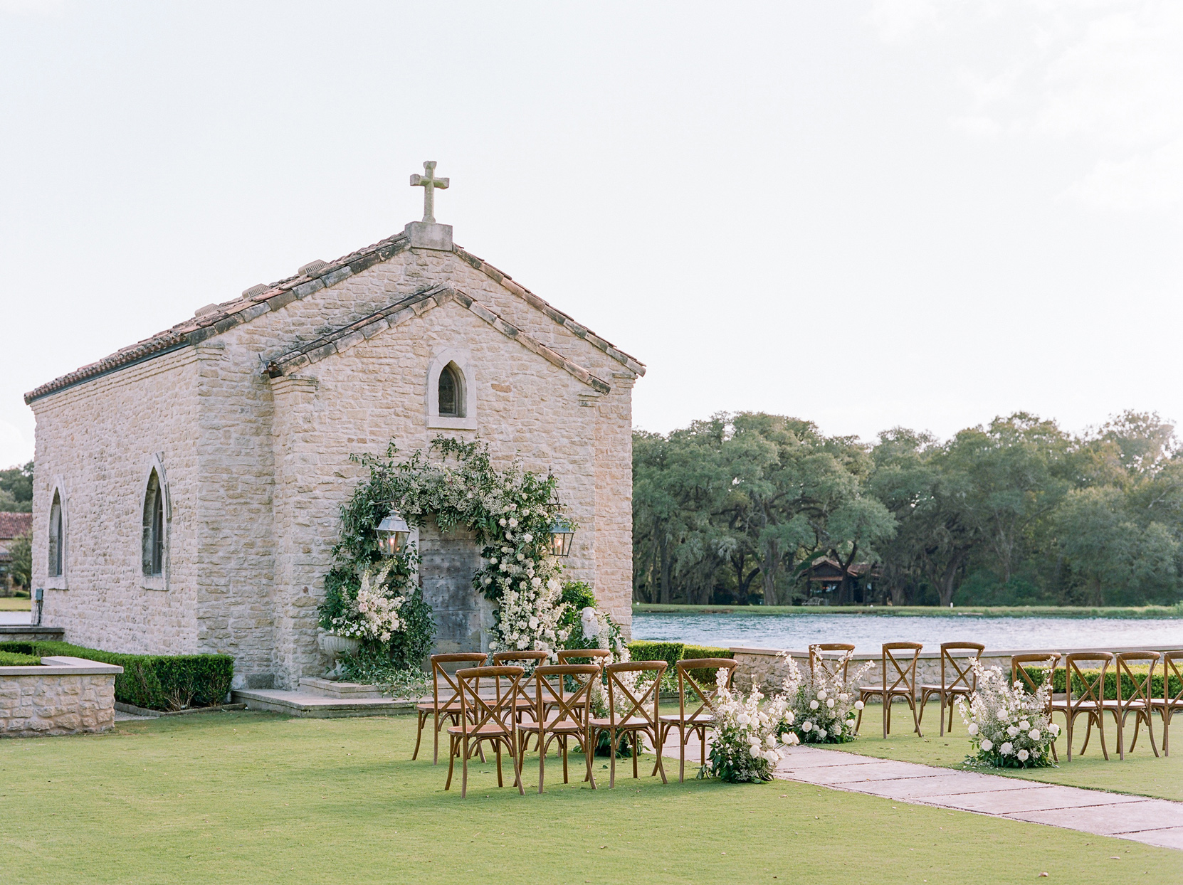 outdoor wedding setup with rows of chairs and a floral archway