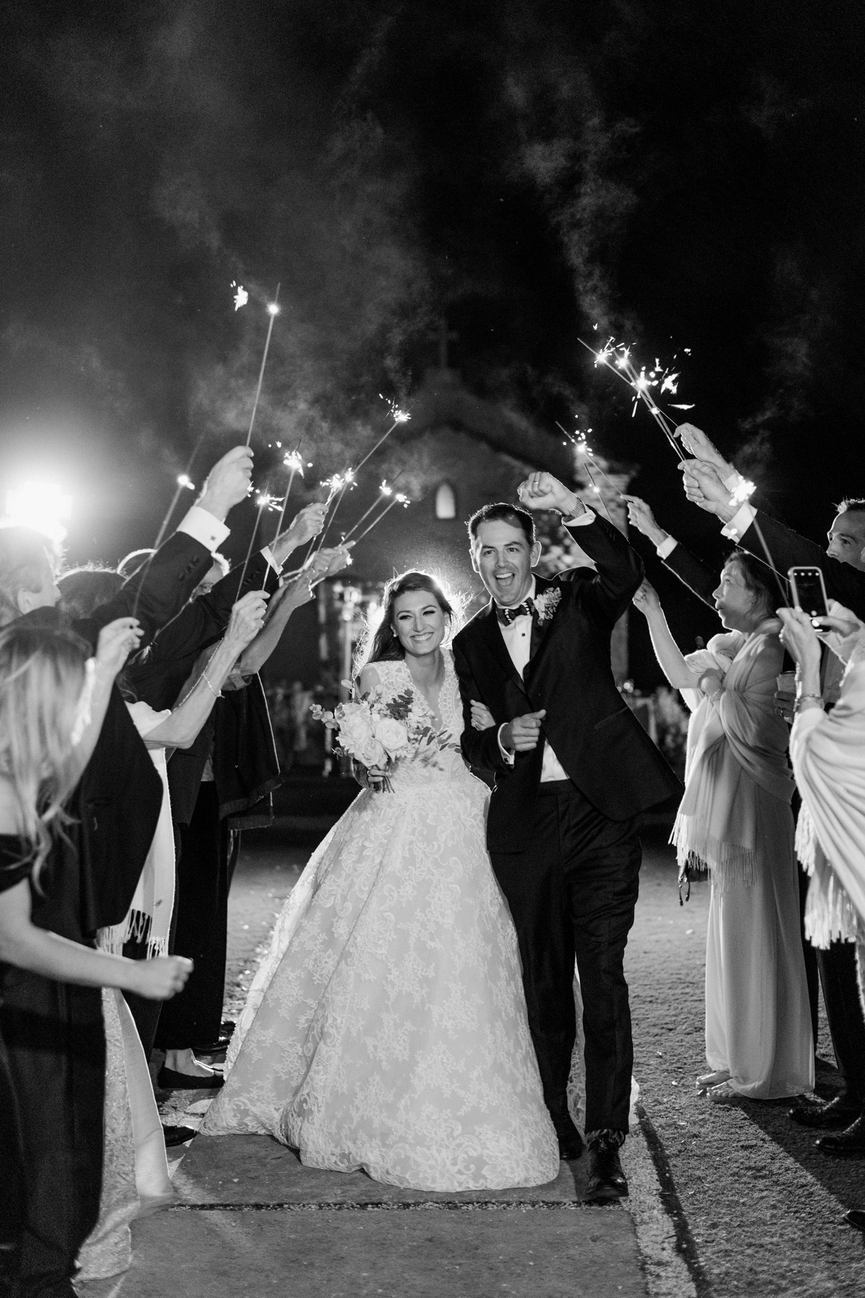 bride and groom leaving reception under sparklers held by guests