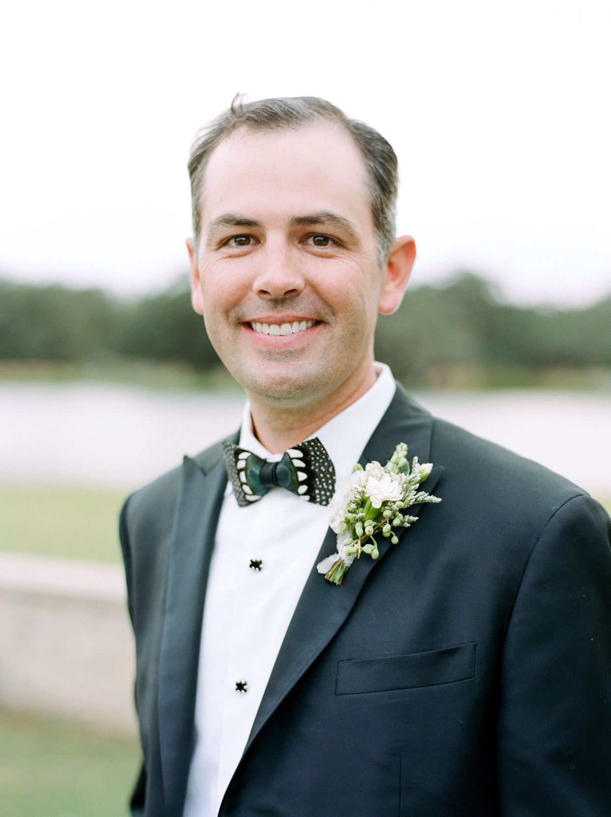 groom in black suite wearing white floral boutonniere