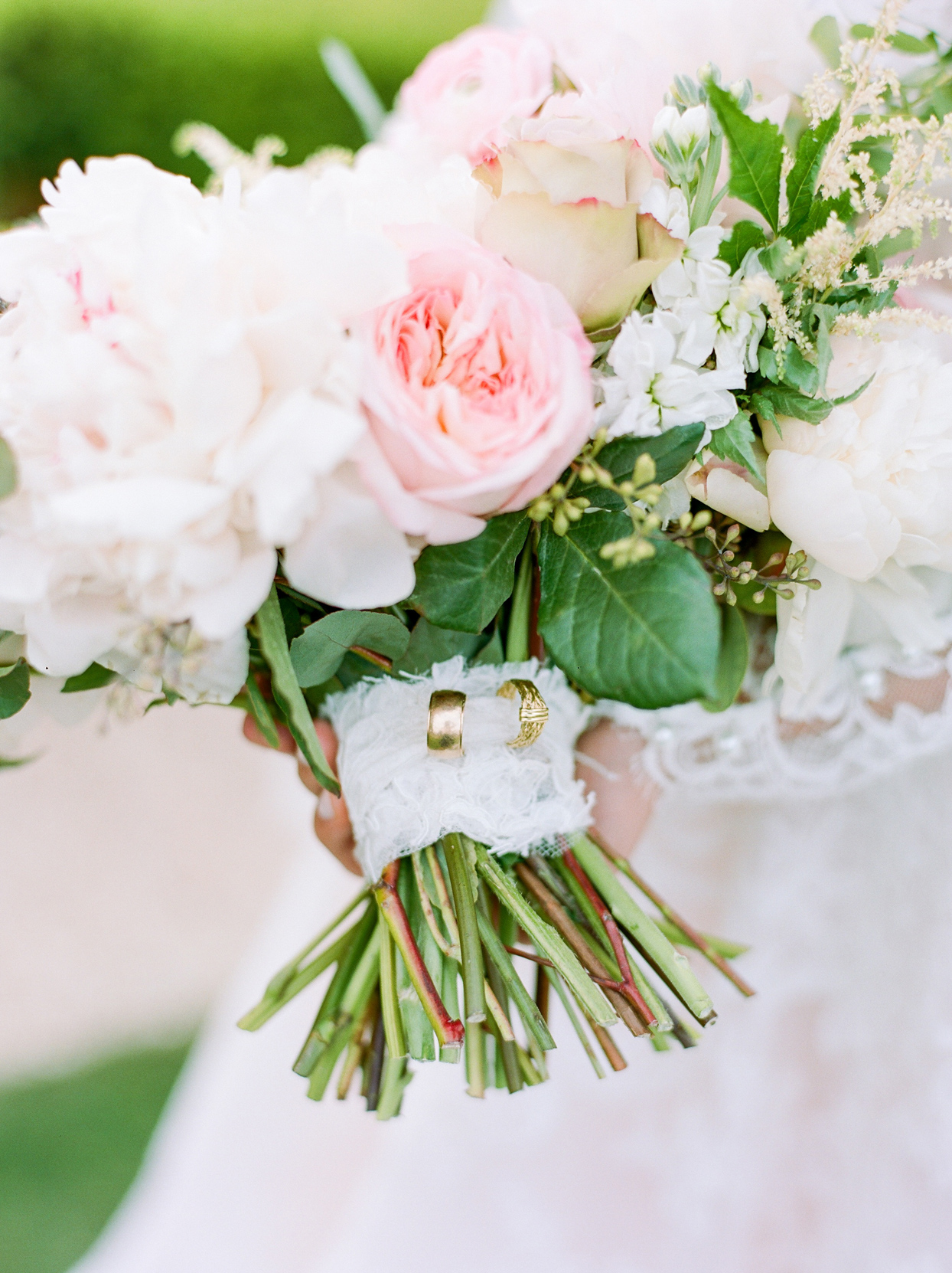 gold wedding rings on bouquet