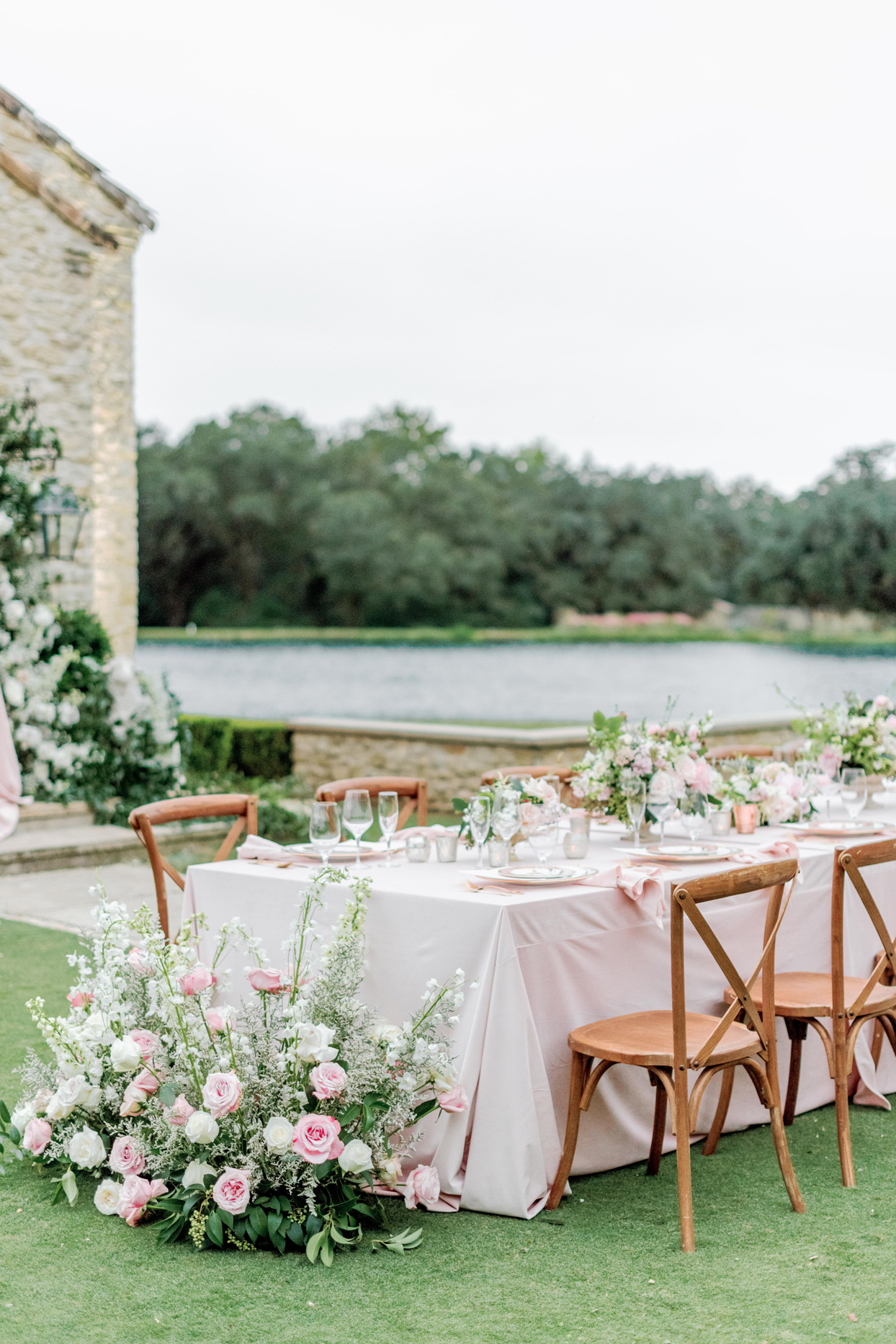 table setting with pink tablecloth and floral arrangements with gold accents