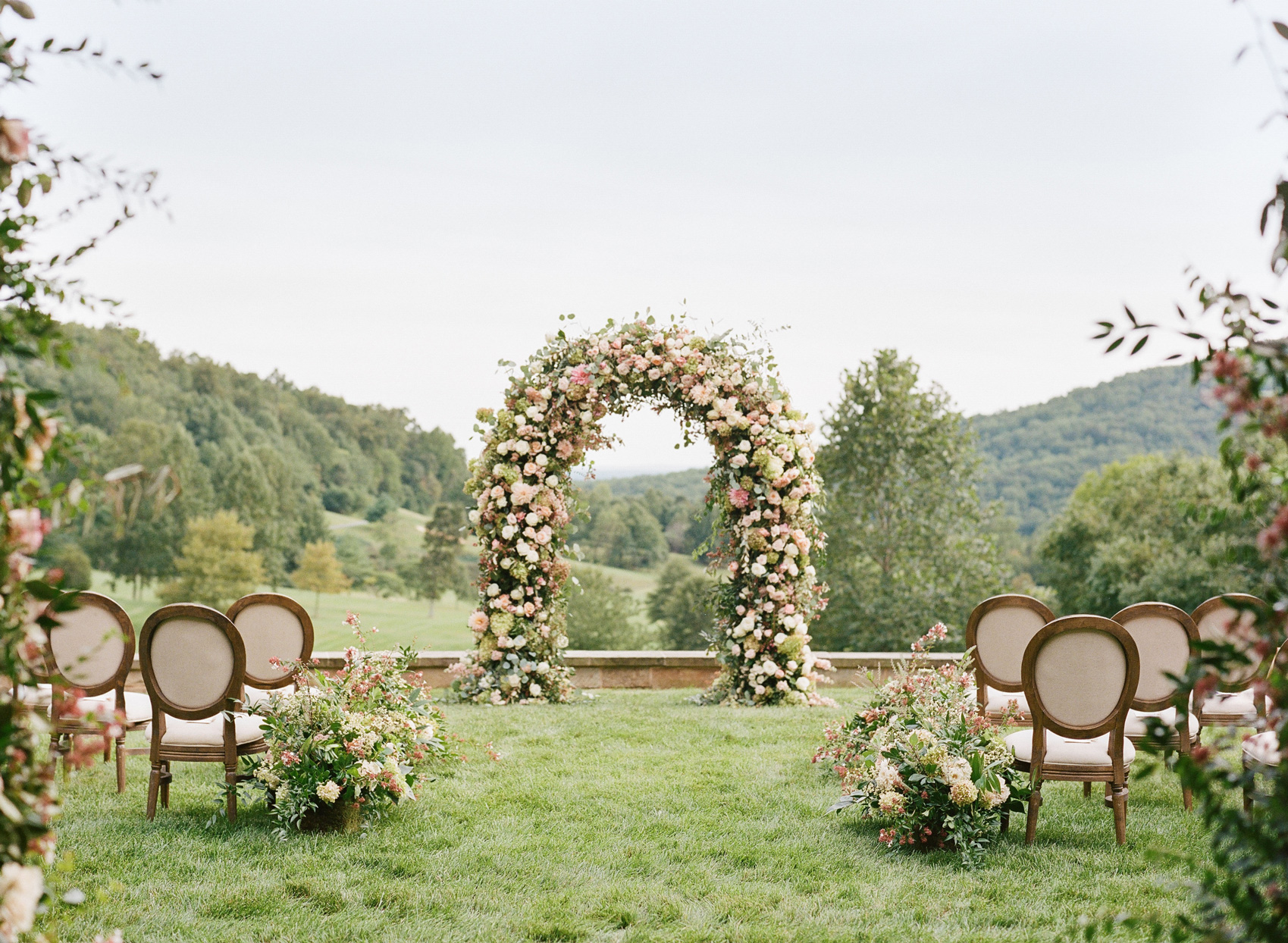 Wedding ceremony arch decorated with pink flowers and greenery