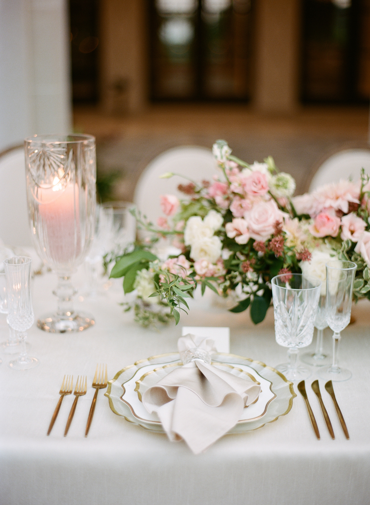 table setting with gold rimmed plates and gold silverware