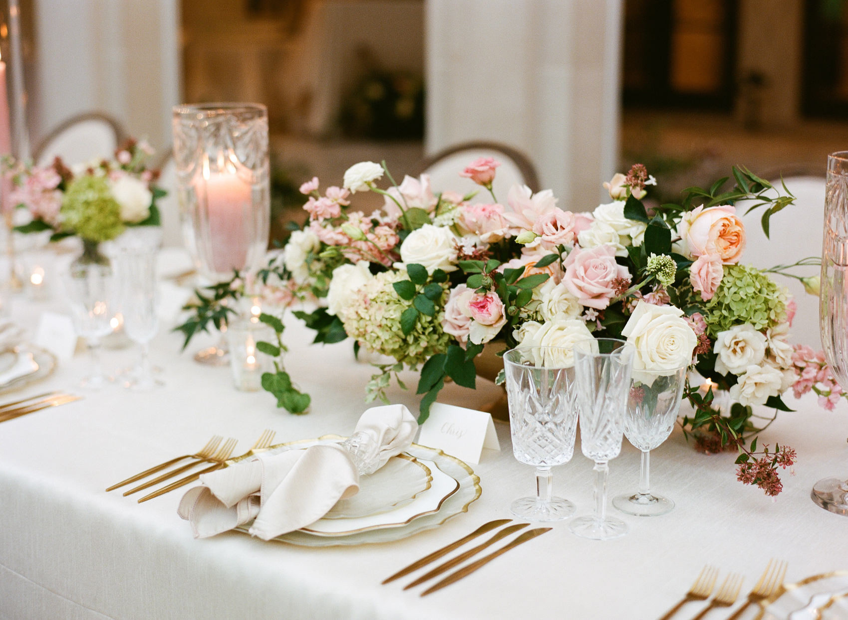 table setting with pink floral arrangements and gold accents