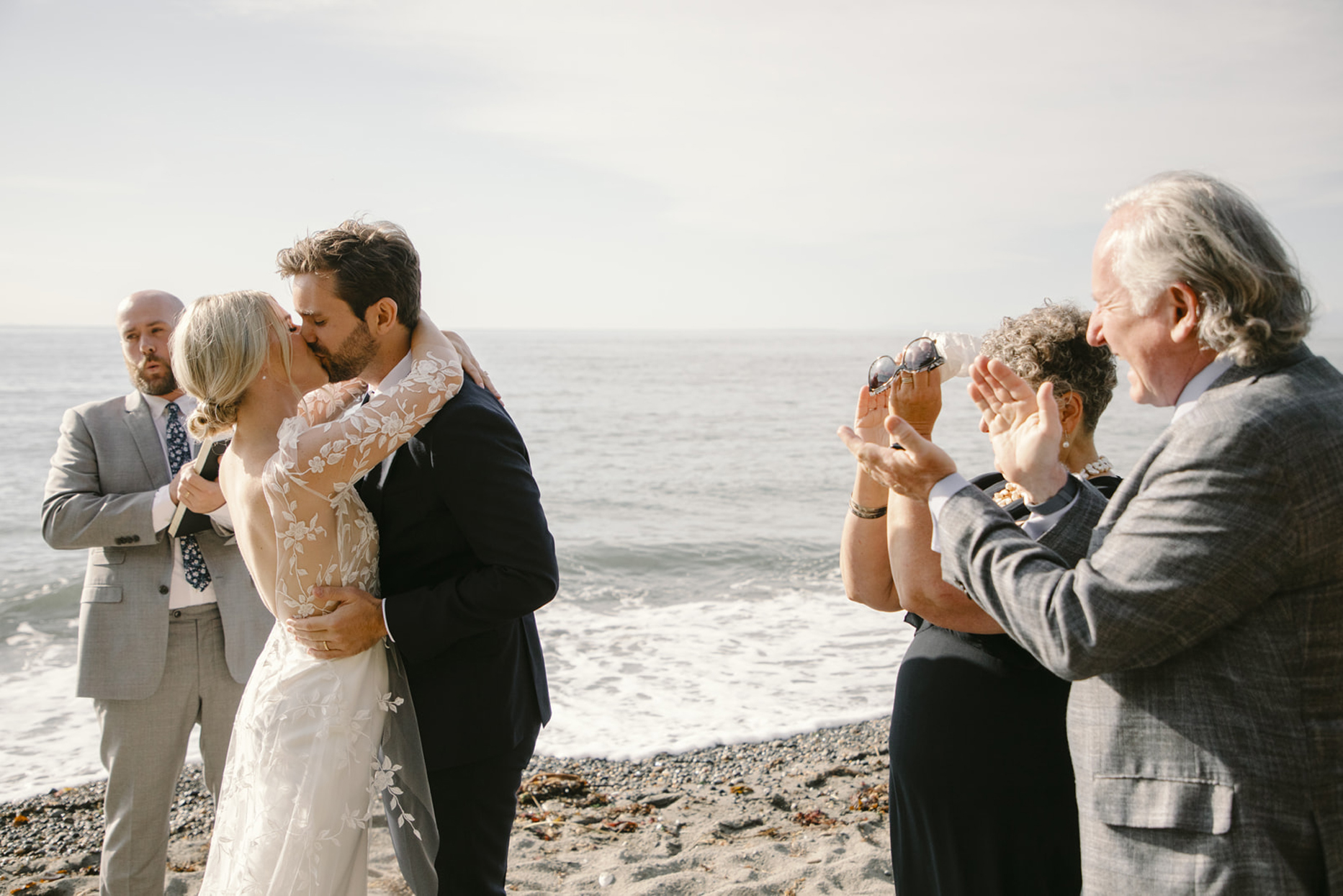 bride and groom kissing on the shore