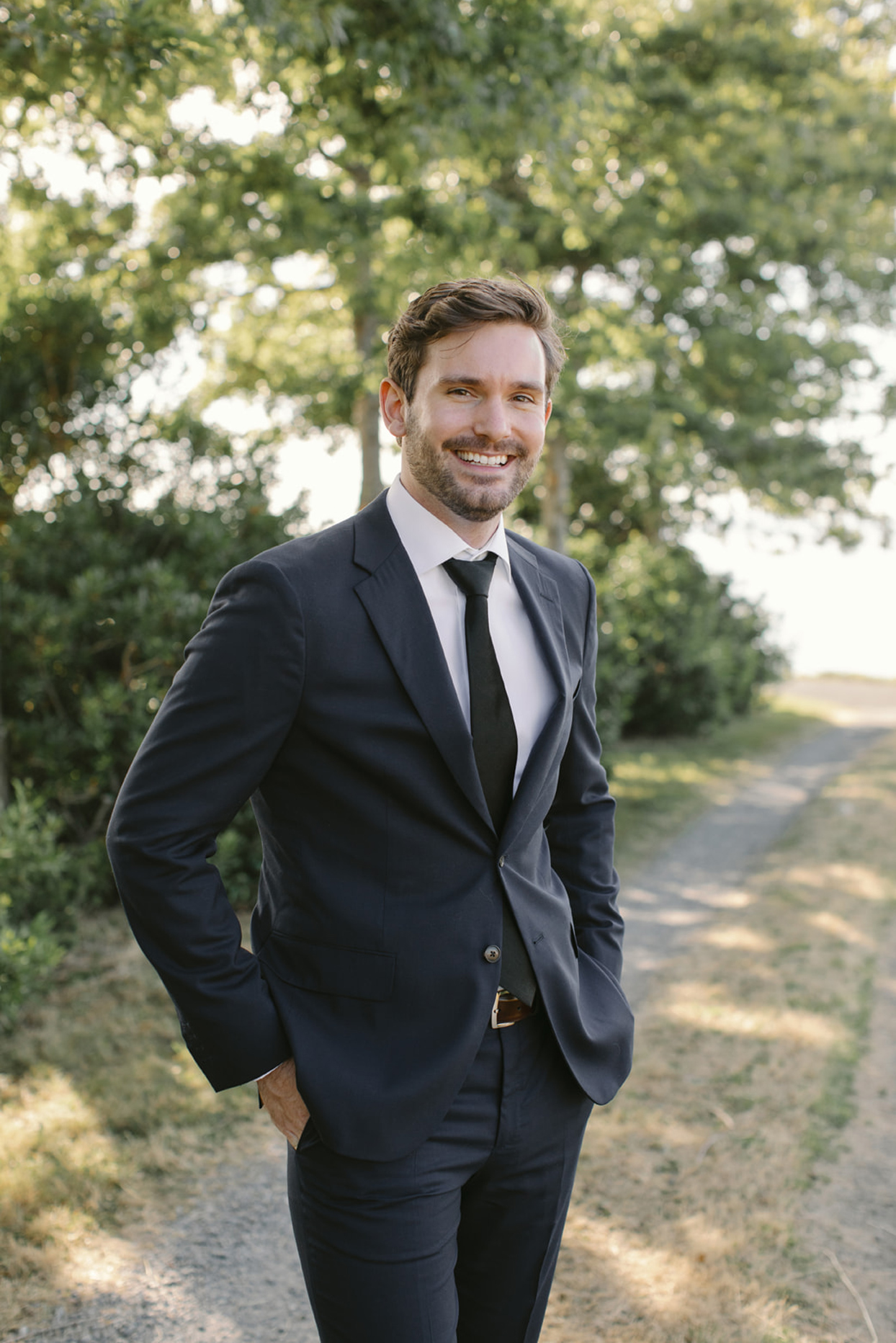 groom in suit outside on the gravel path