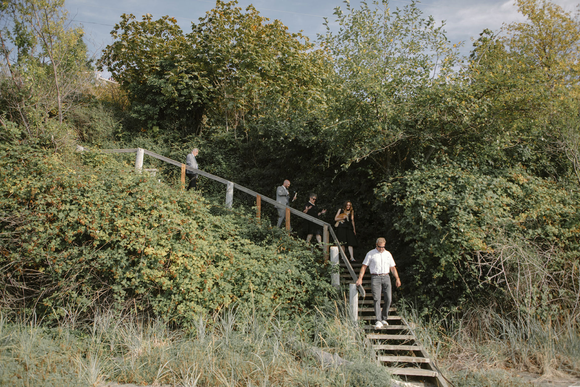 wedding guests walking down wooden stairs