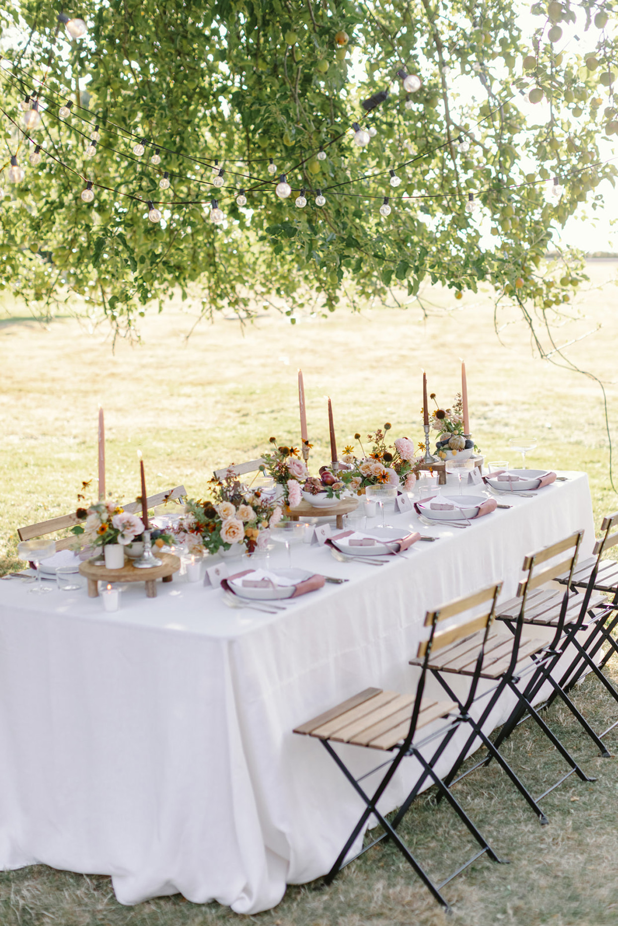 dinner table set with pink flowers and candles