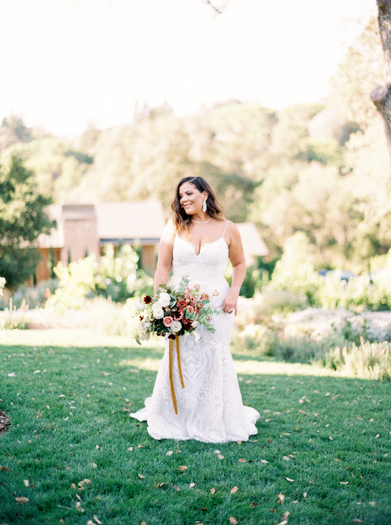 bride holding fall floral bouquet in grassy field