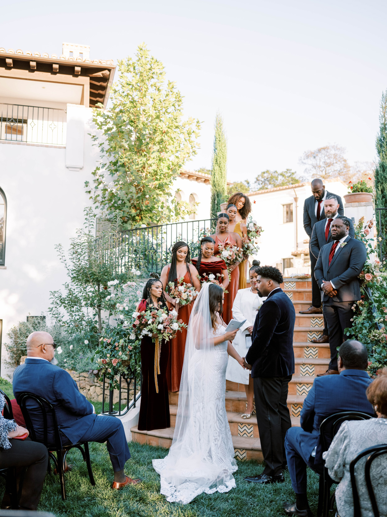 couple exchanging vows for small ceremony with wedding party standing on stairs above