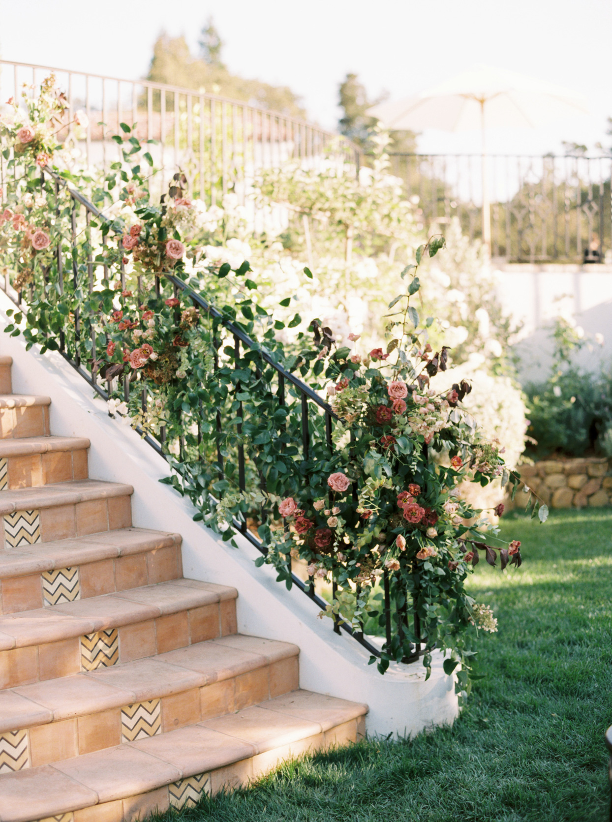 patterned steps down to wedding ceremony grassy landing with flowers on the bannister