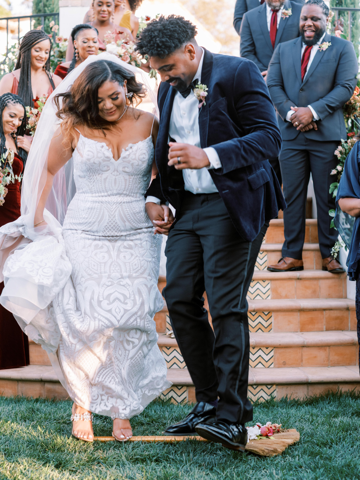 couple jumping on broom during wedding ceremony