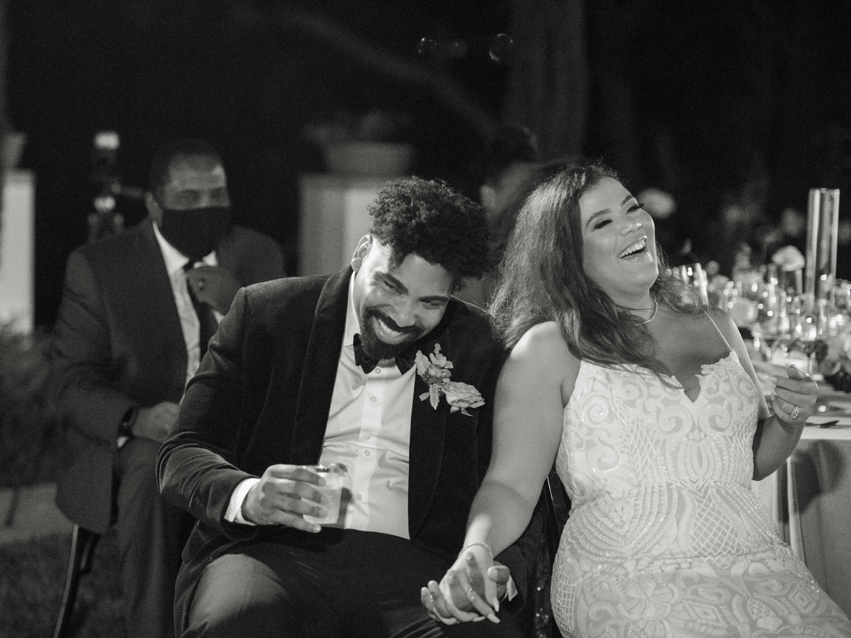 couple holding hands and laughing during wedding reception