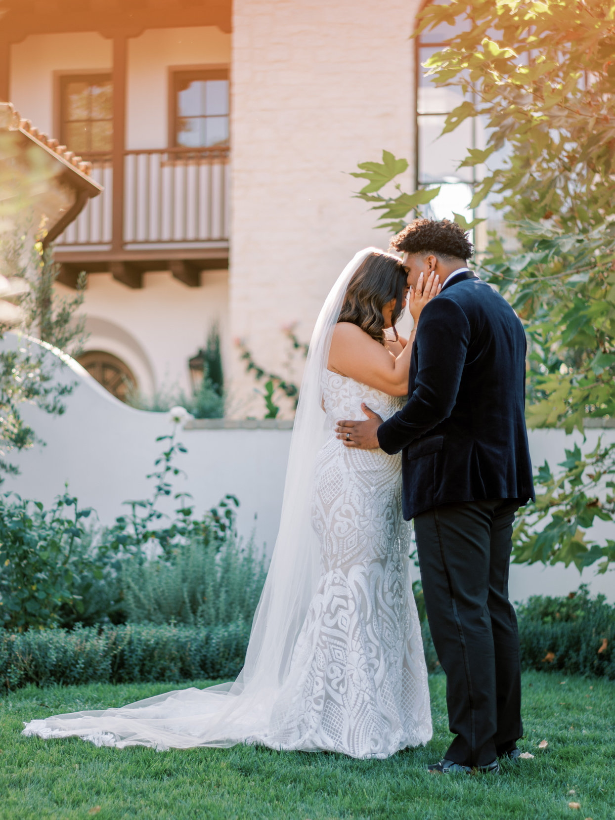 couple embracing during first look on grassy lawn