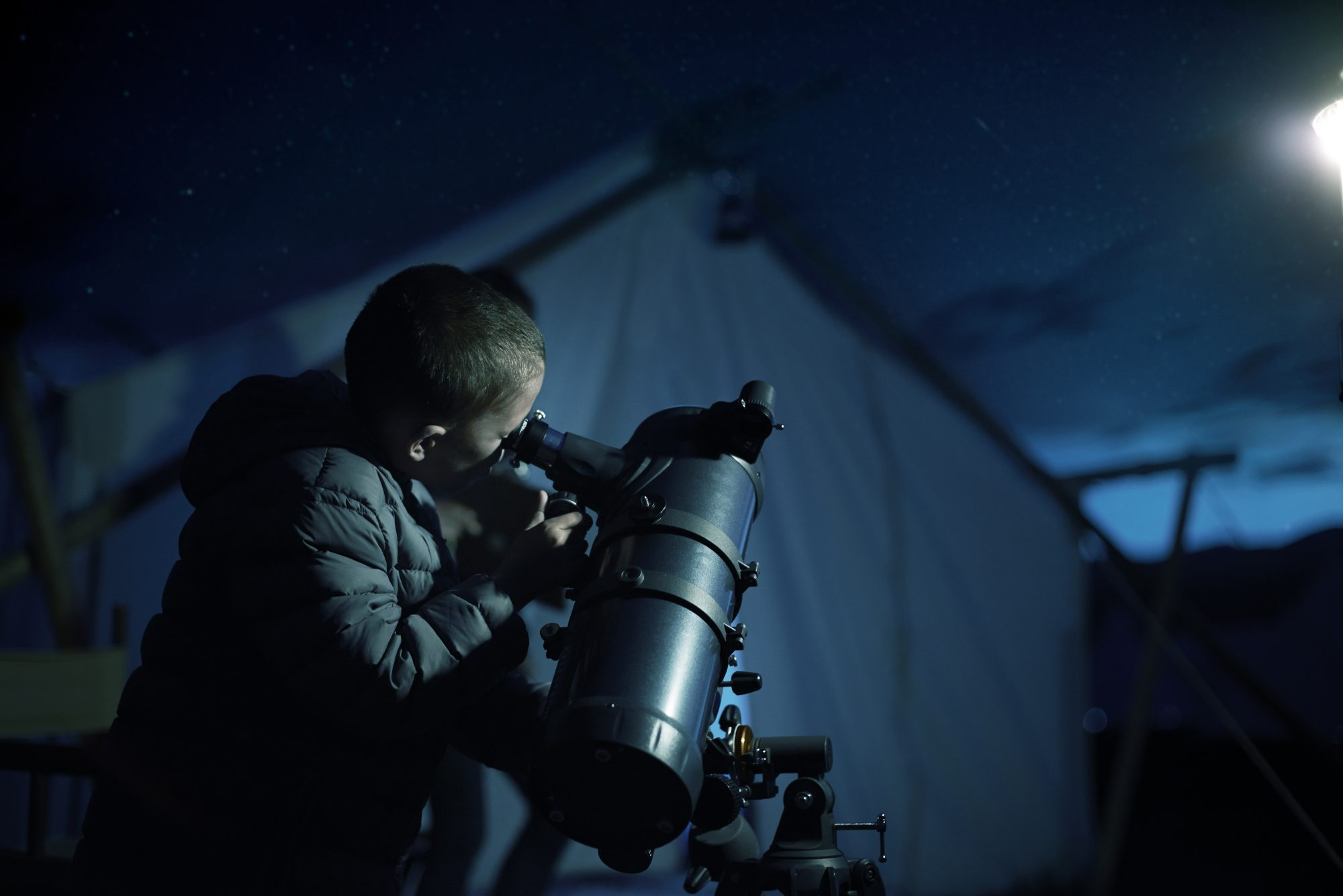boy looking though telescope at night