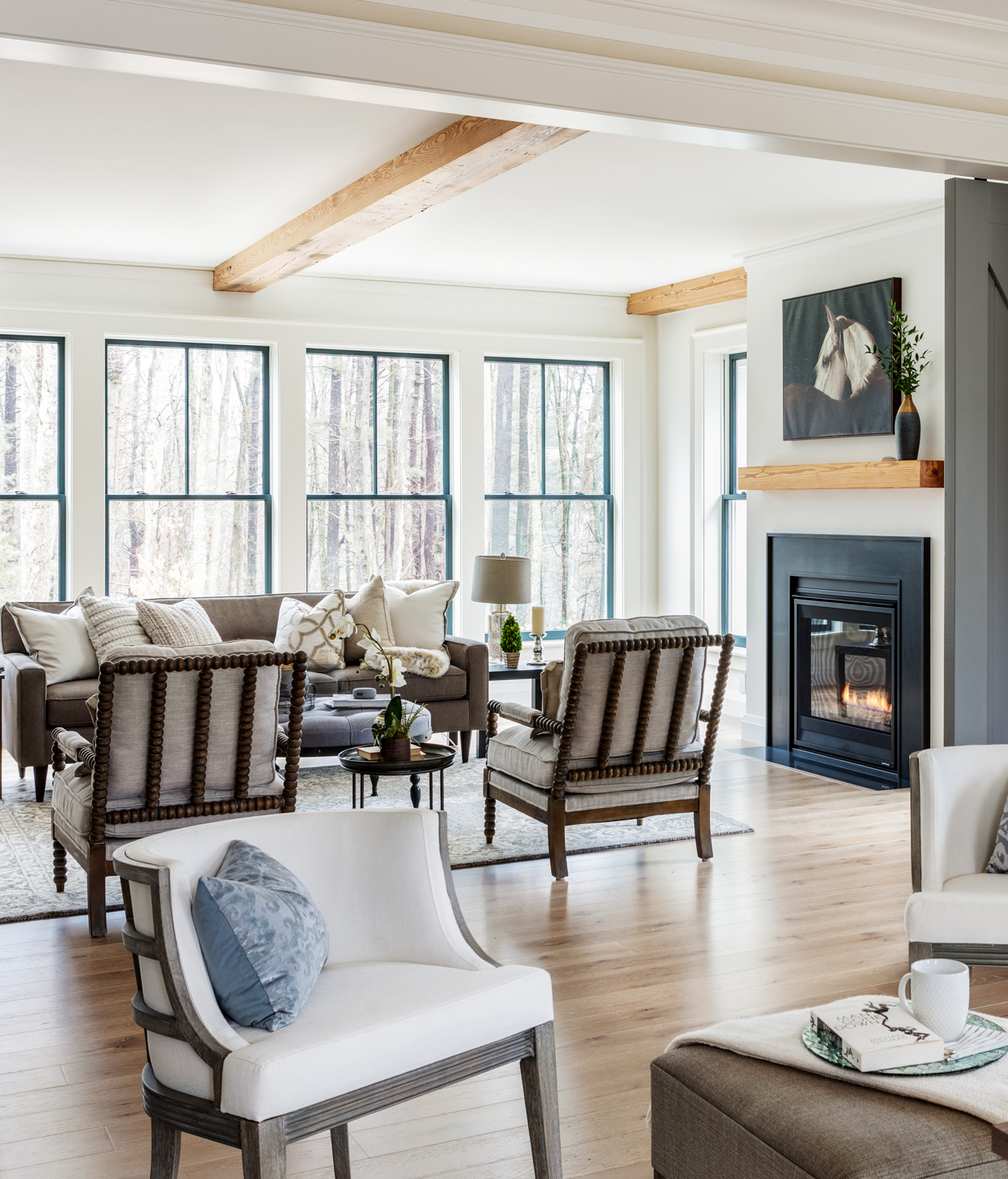 white living room with fireplace and natural wood beams