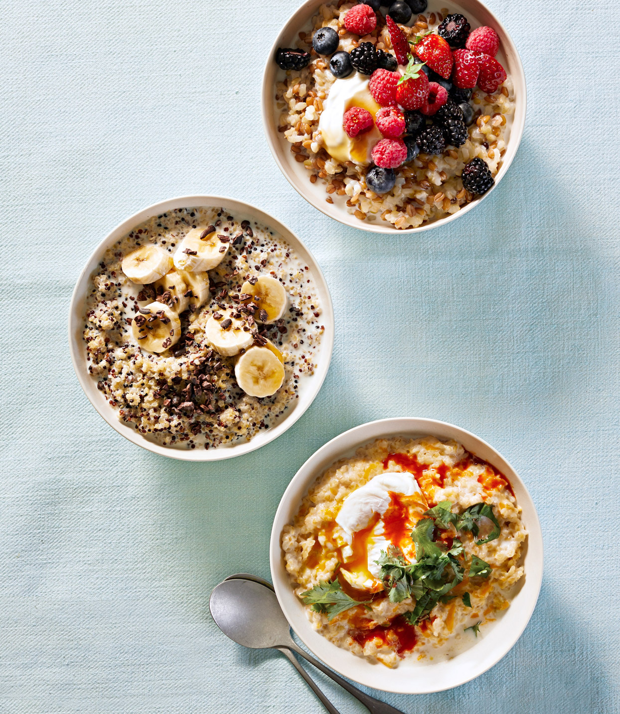 three different types of breakfast bowls on pale blue linen tablecloth