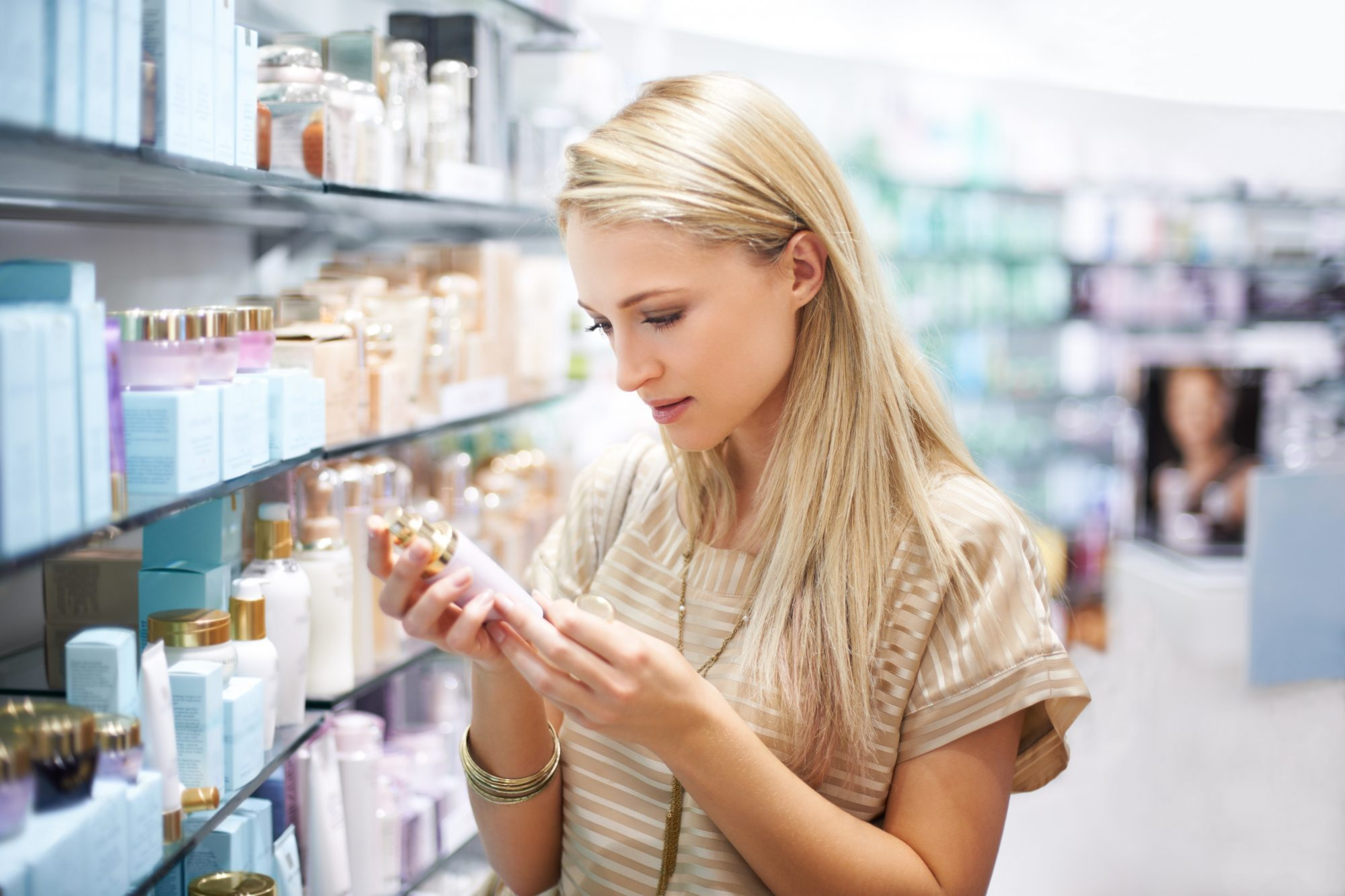 woman reading beauty product ingredients on back of bottle