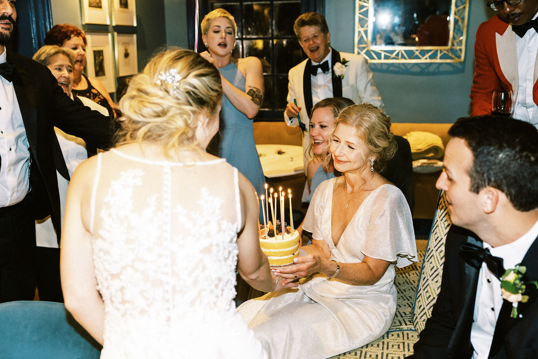 guests smiling and singing with lit birthday cake