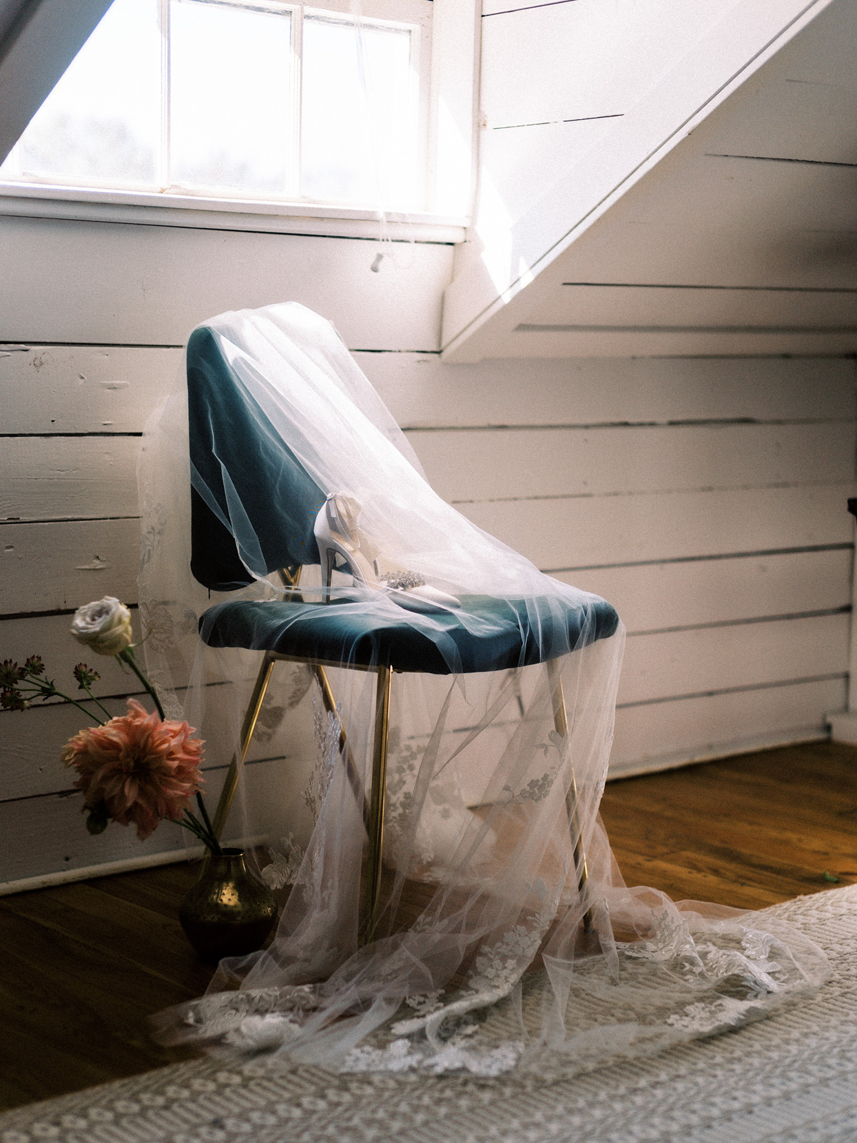 antique chair with wedding accessories sitting on it in attic corner