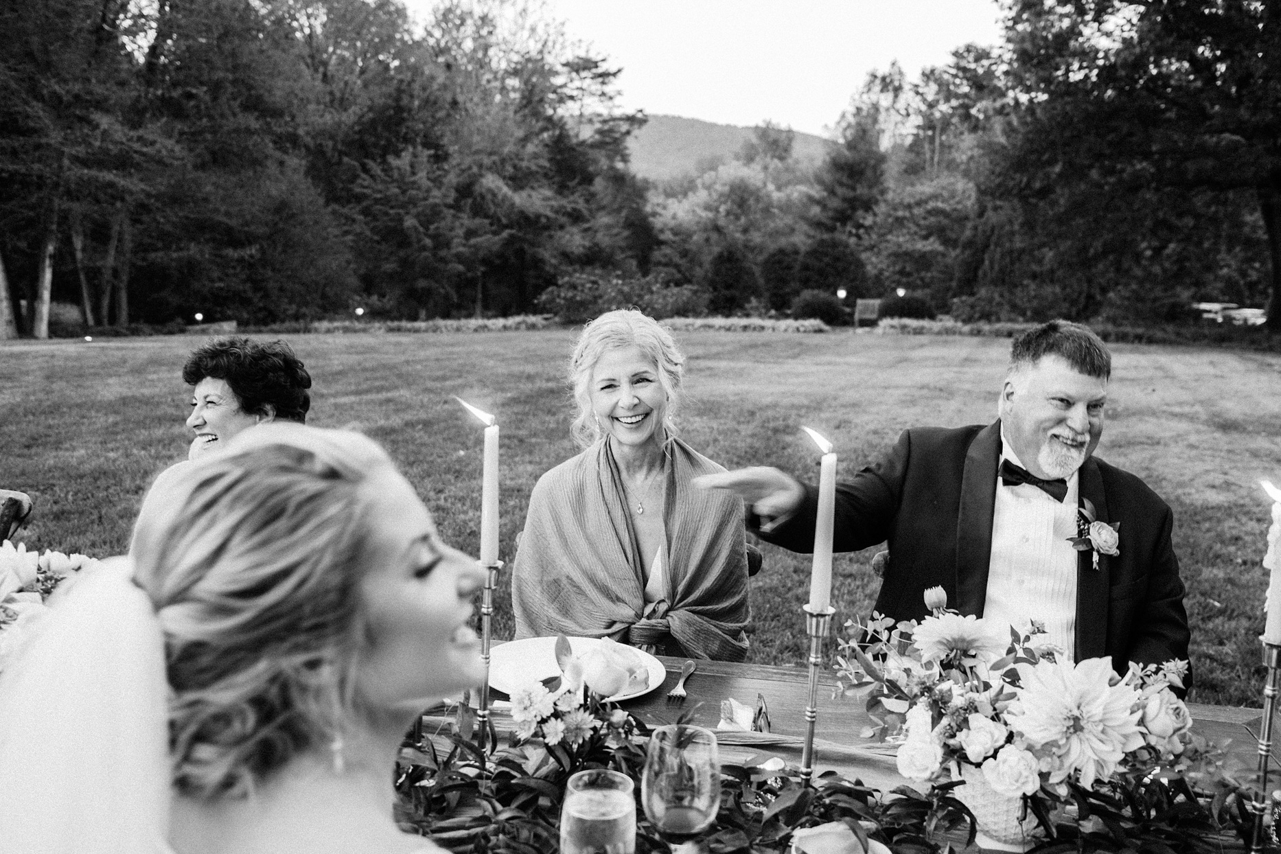 parents smiling at wedding reception table outdoors