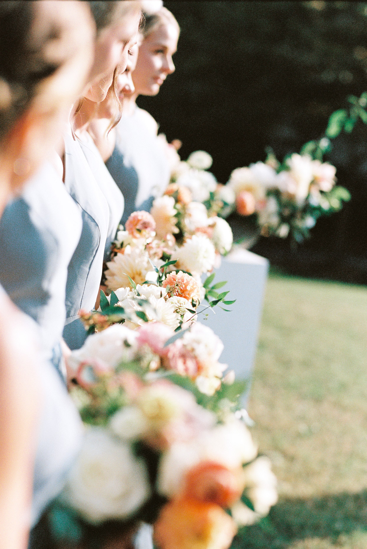 bridesmaids in pastel blue dresses holding pink and orange bouquets