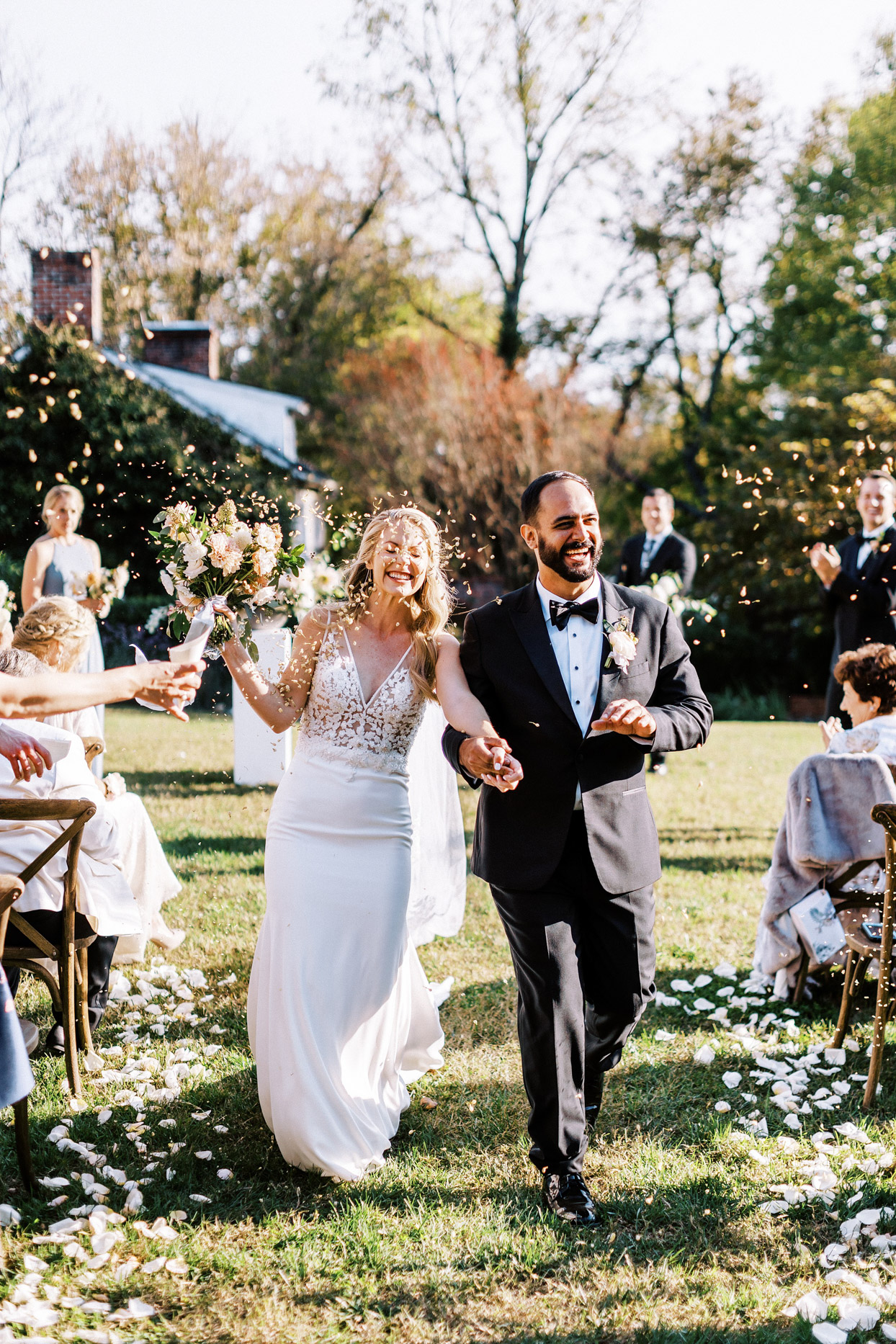 couple recessing at outdoor ceremony while guests shower them in flower petals