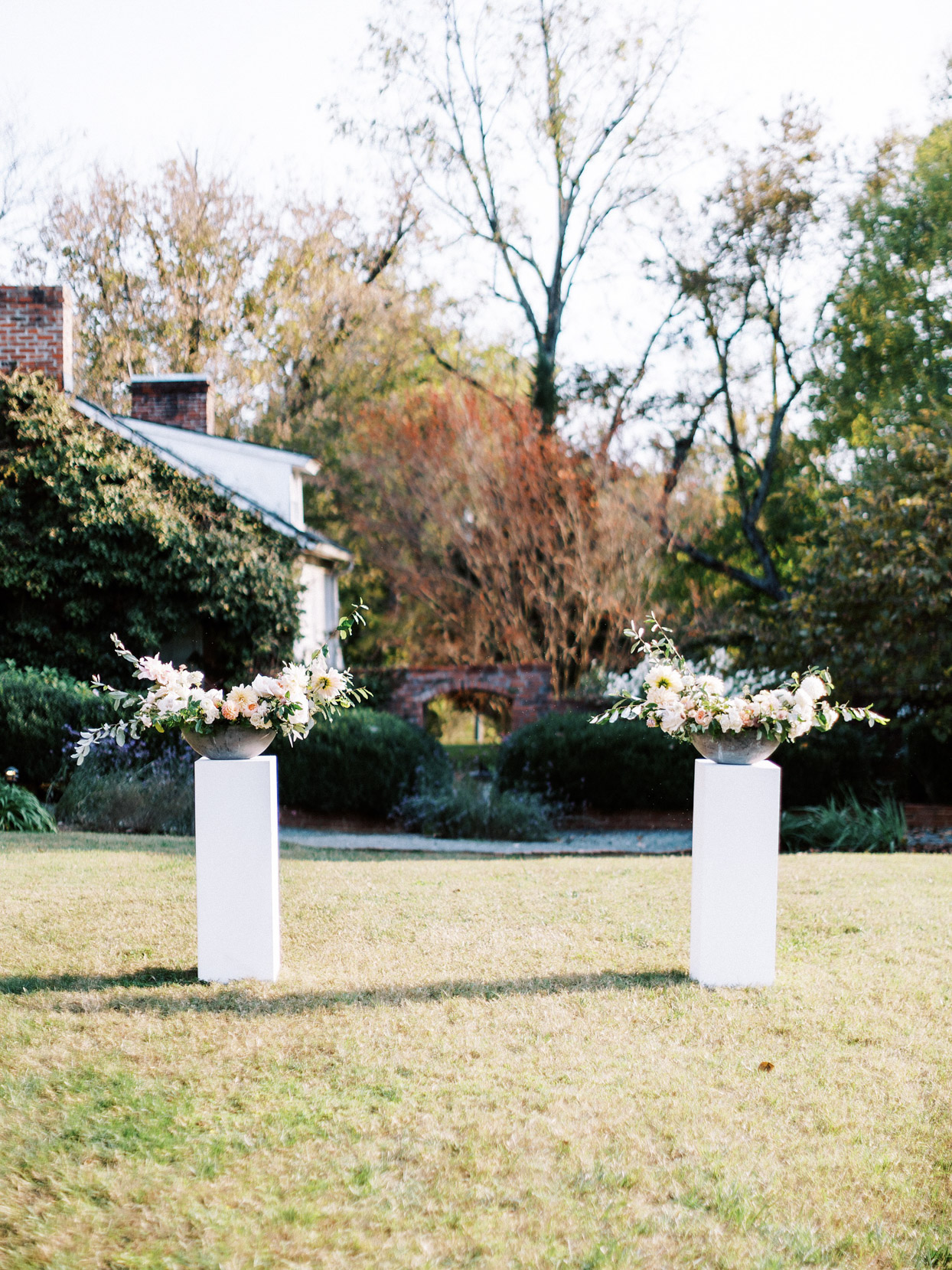 outdoor ceremony space with pillars with floral bouquets on top
