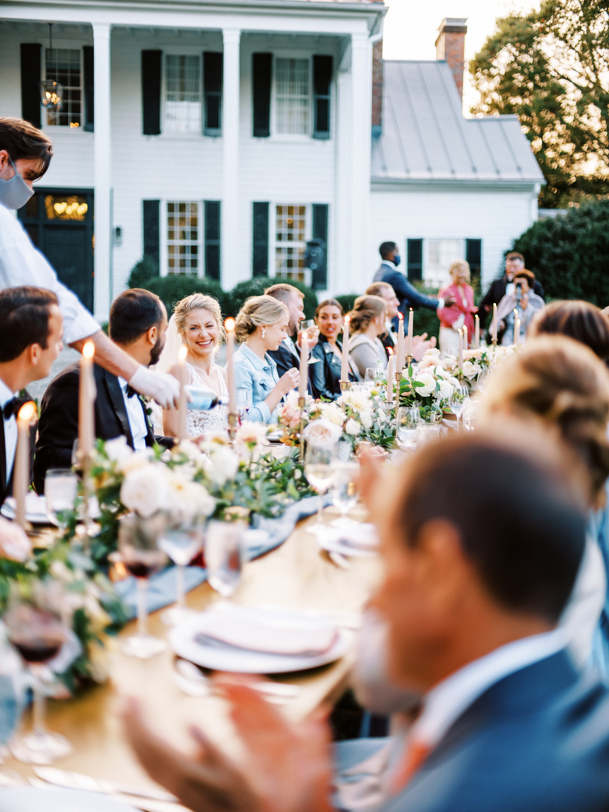 long outdoor table with guests eating wedding dinner
