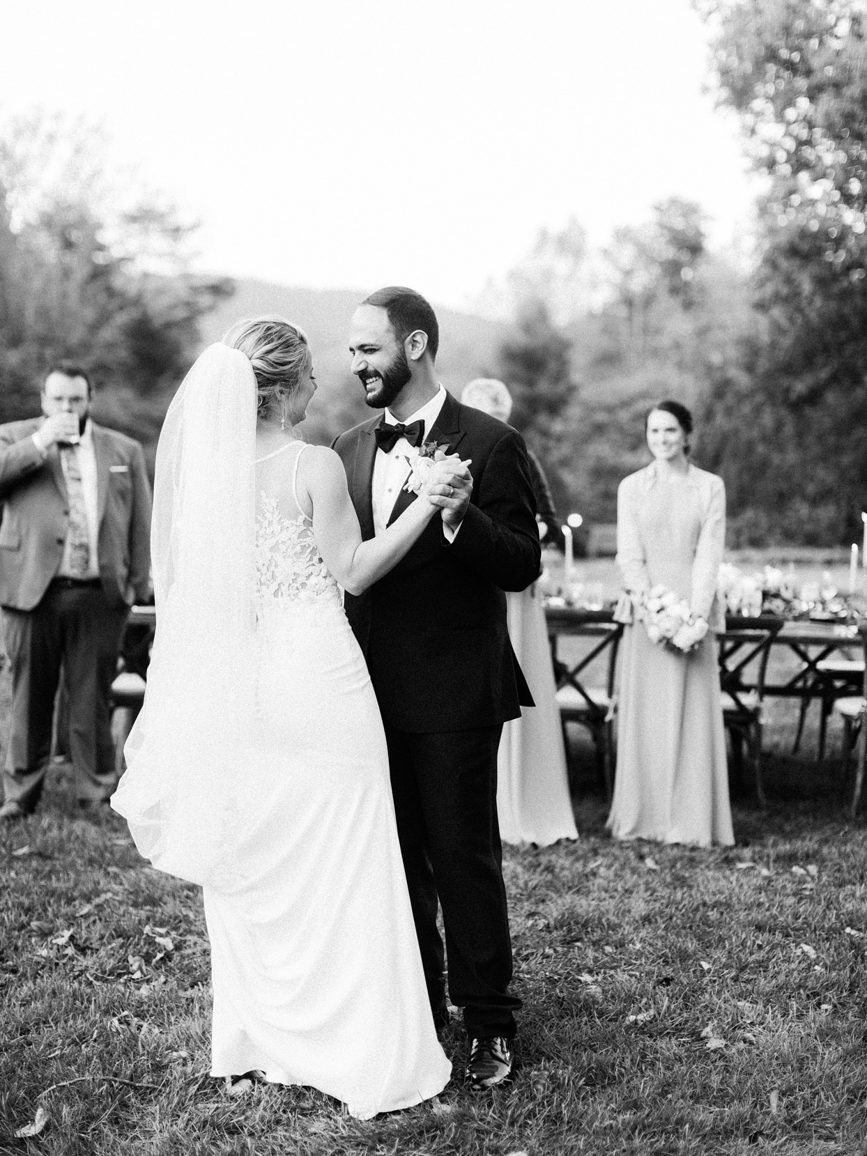 couple having first dance outdoors with guests watching at tables