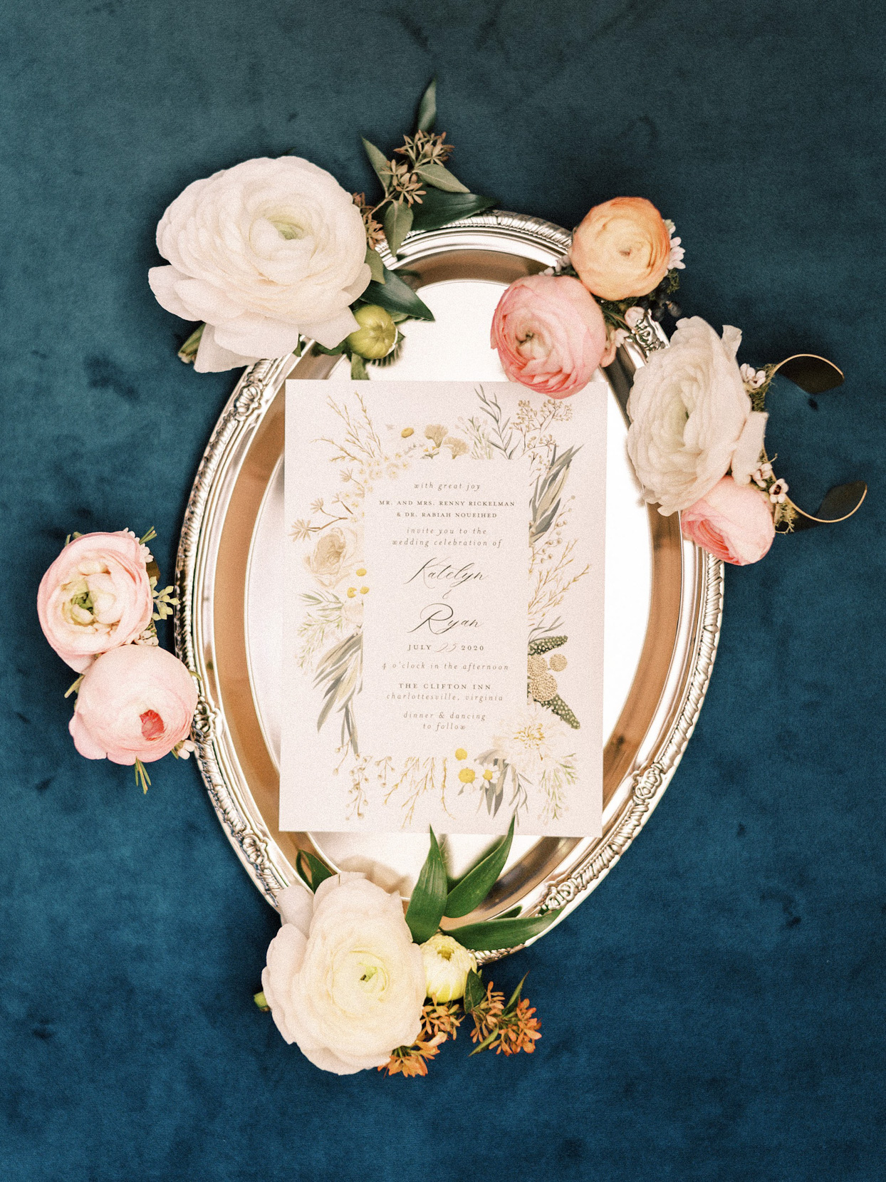 silver tray with floral boutonnières and elegant invitations