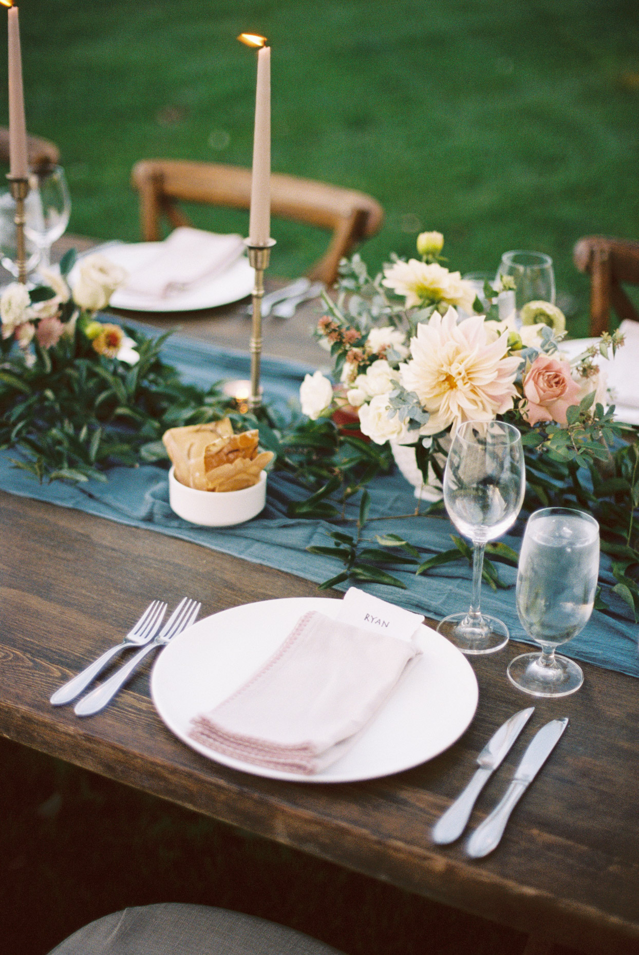 close up of wooden reception table with blue runner and orange and pink flowers