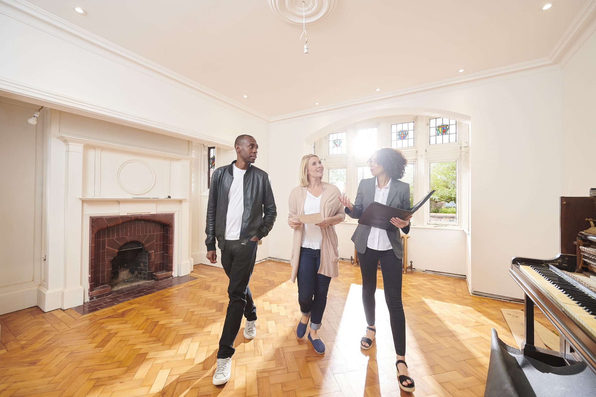 couple inspecting home with real estate agent