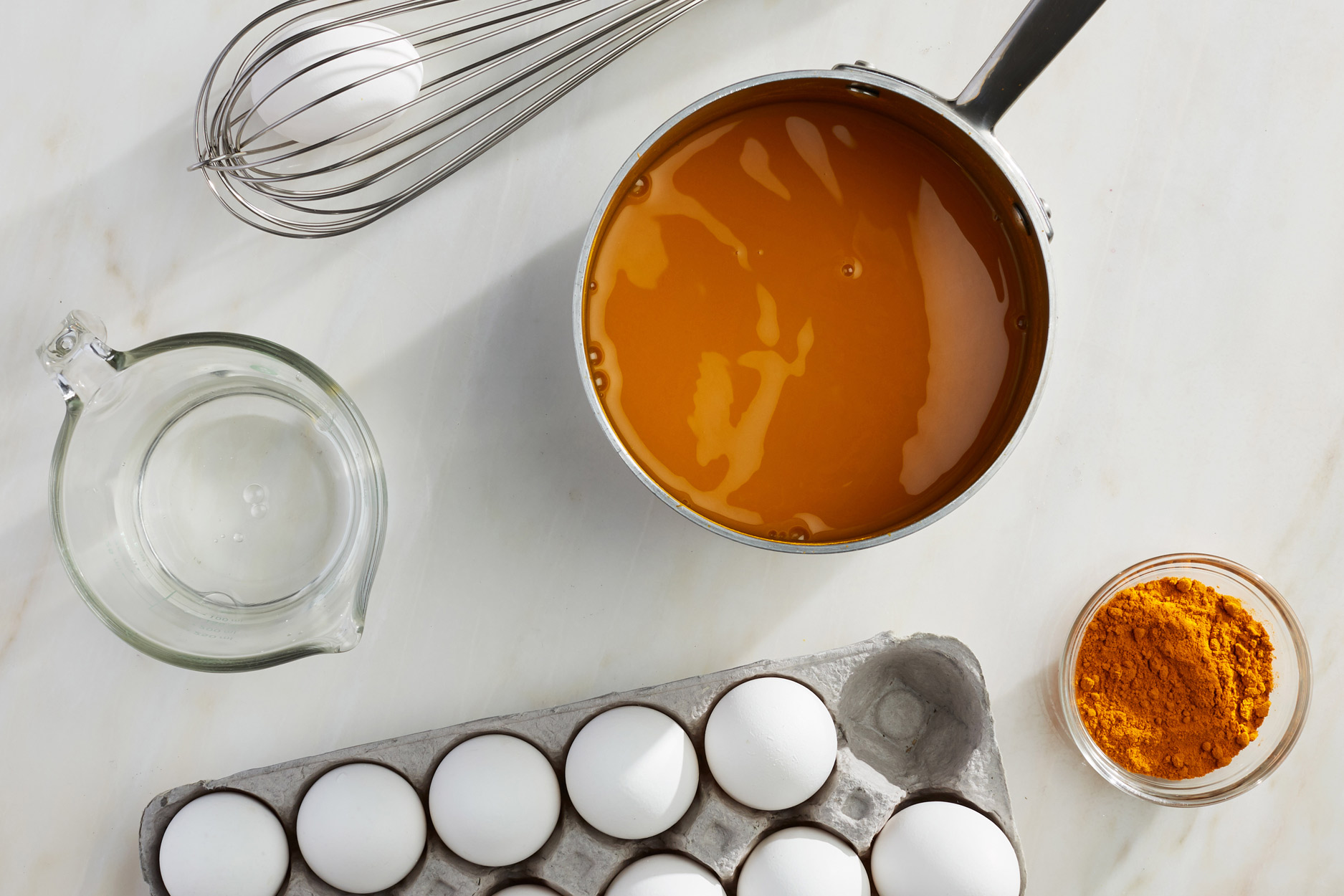 a carton of eggs and a pot with an orange powder mixture