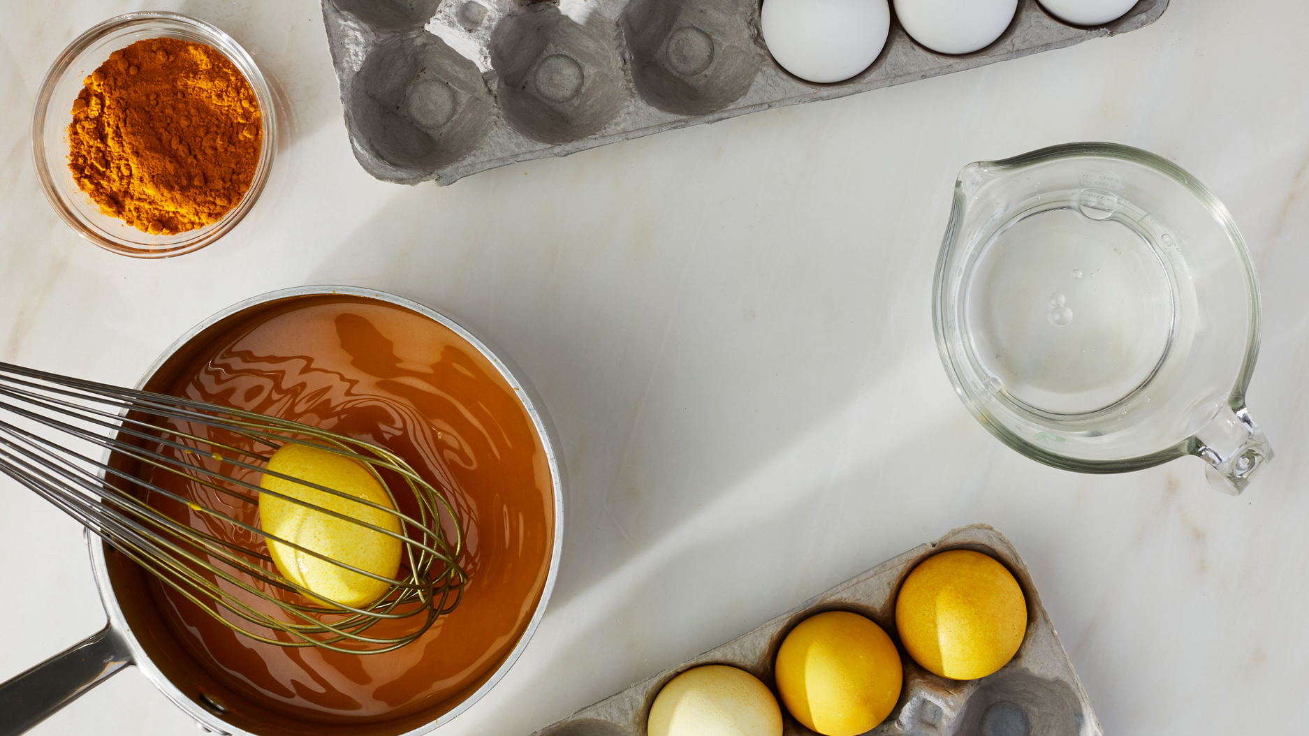 whisking an egg in a pot with orange dye