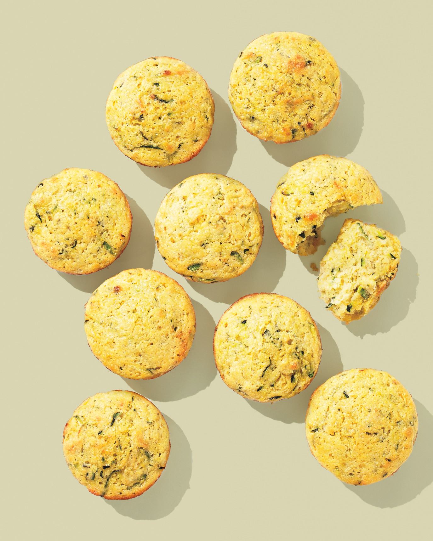 multiple zucchini muffins on surface