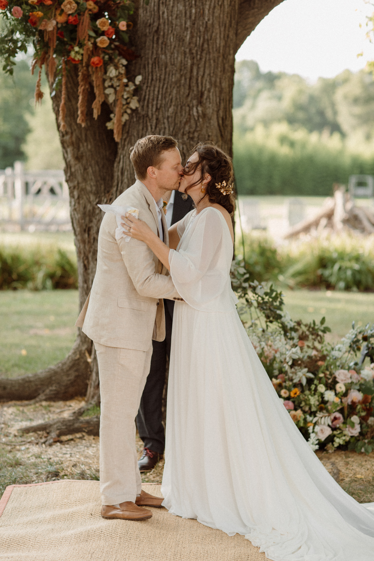 bride and groom share a kiss under backyard wedding ceremony tree