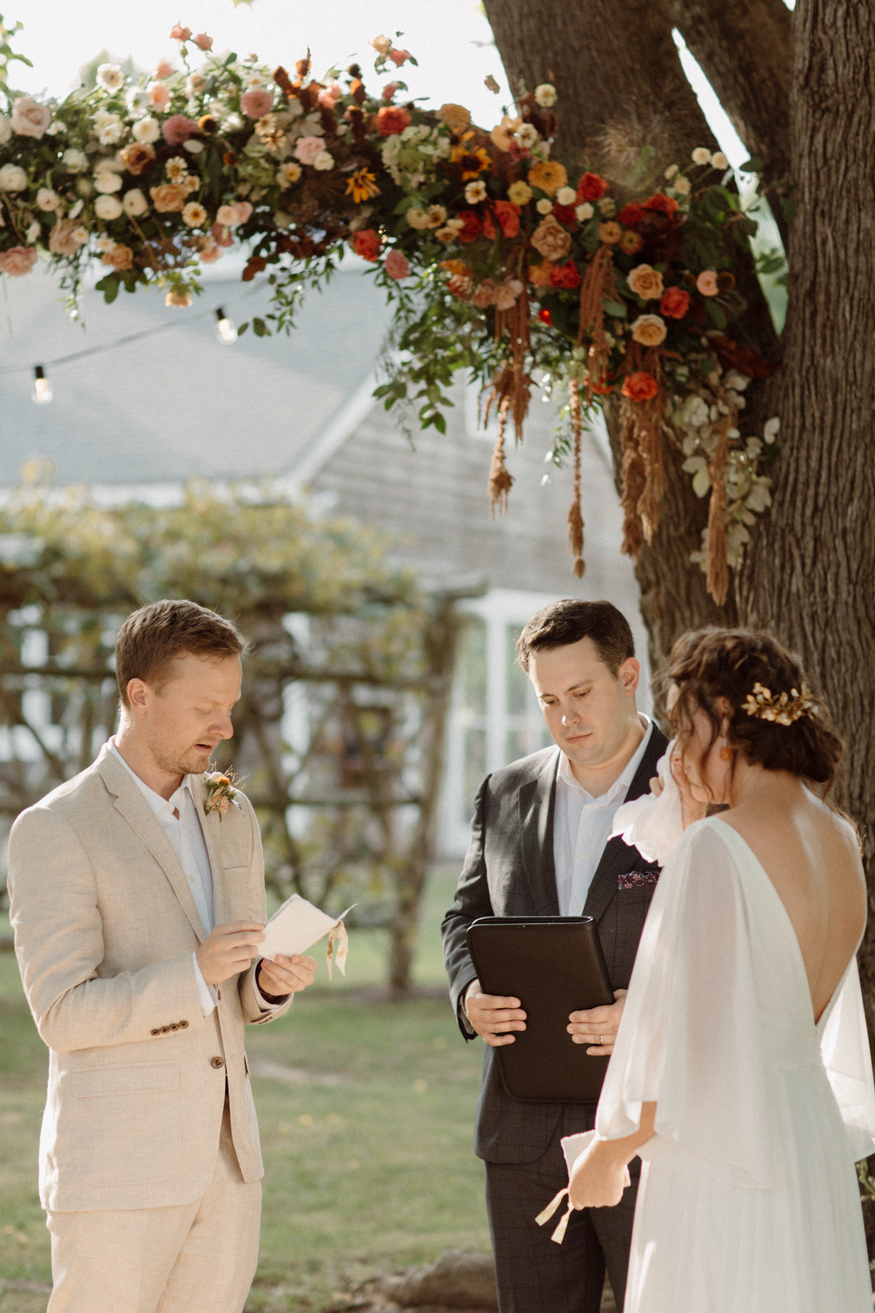 bride and groom exchanging vows during backyard ceremony