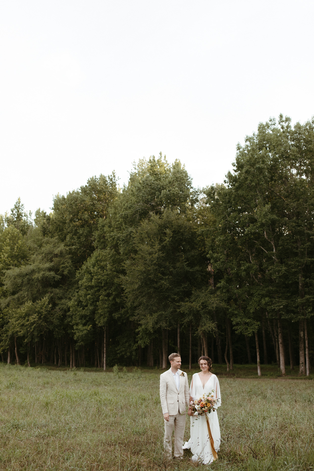 bride and groom stand in grassy field by wooded area