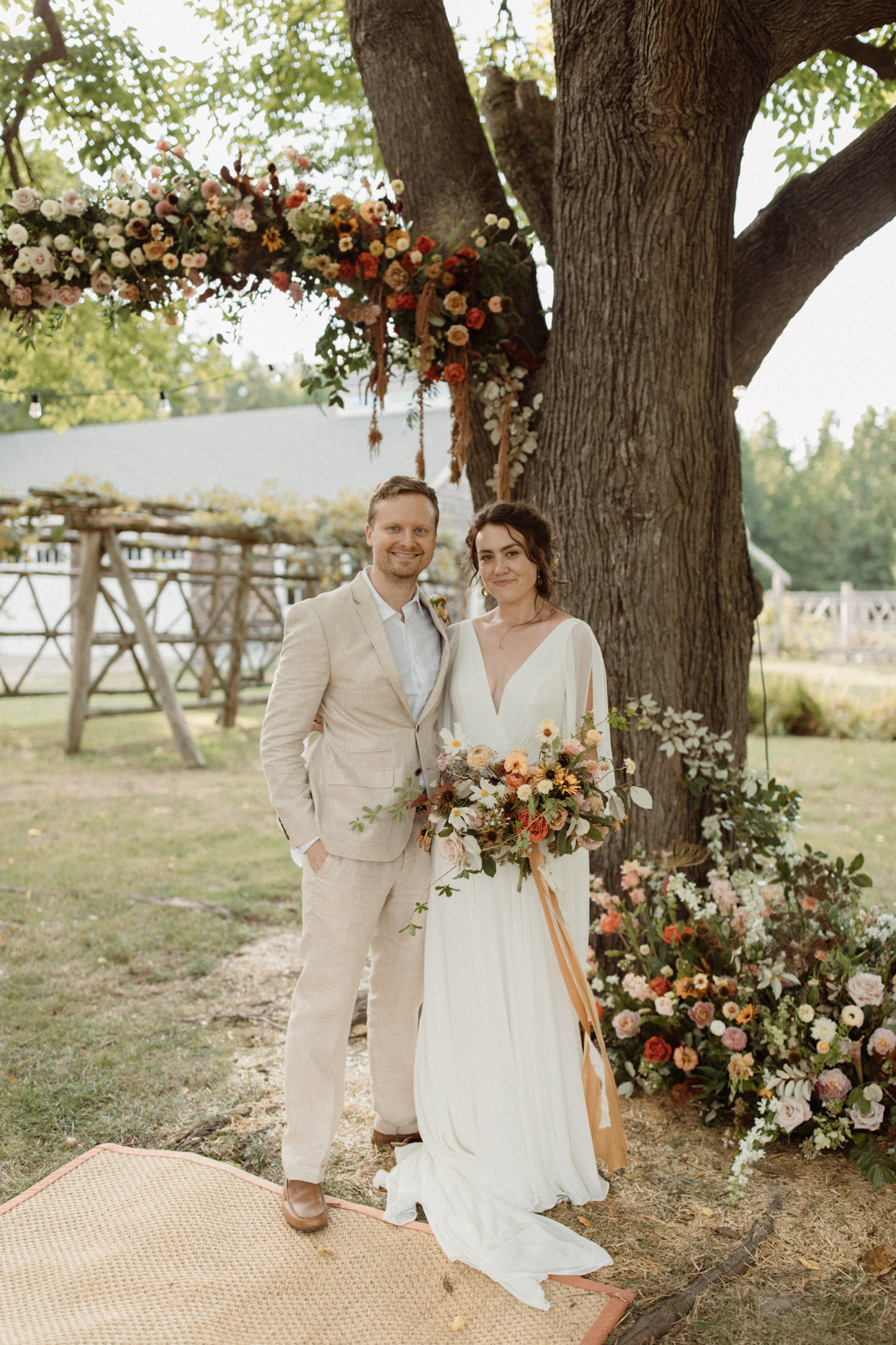 bride and groom smiling under large backyard tree wedding ceremony space